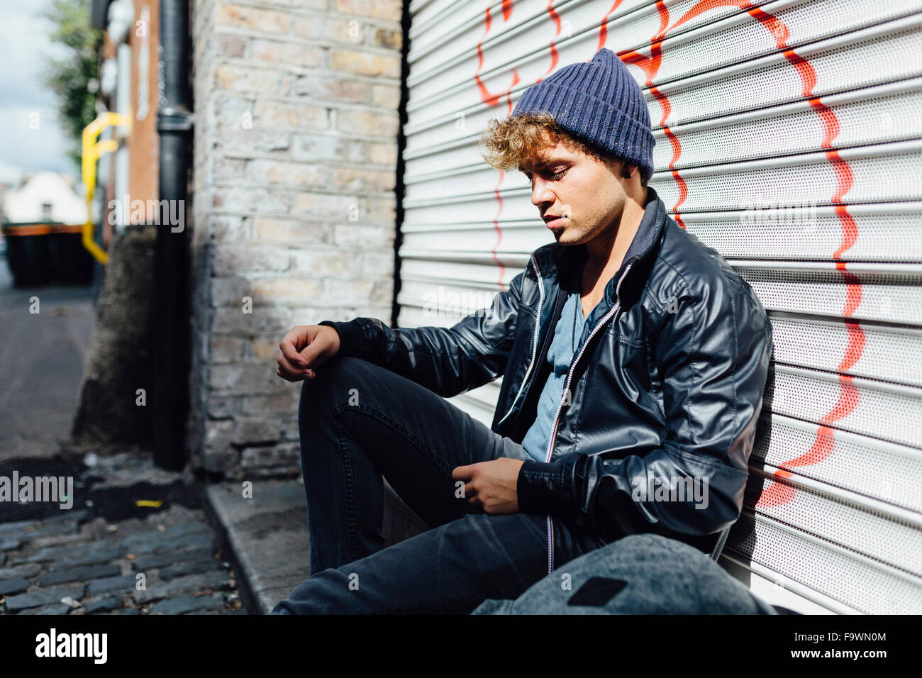 Young man leaning against roller shutter - Stock Image