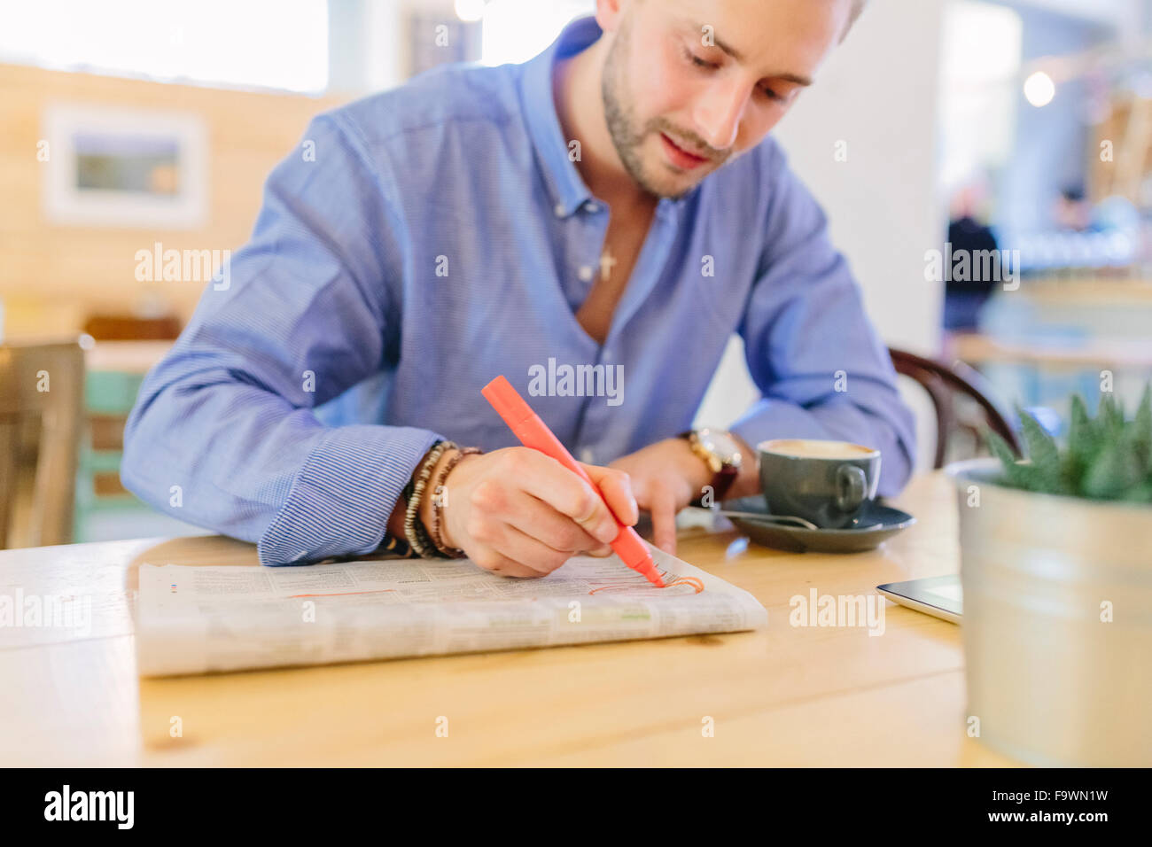 Man sitting in a coffee shop marking something in a newspaper - Stock Image