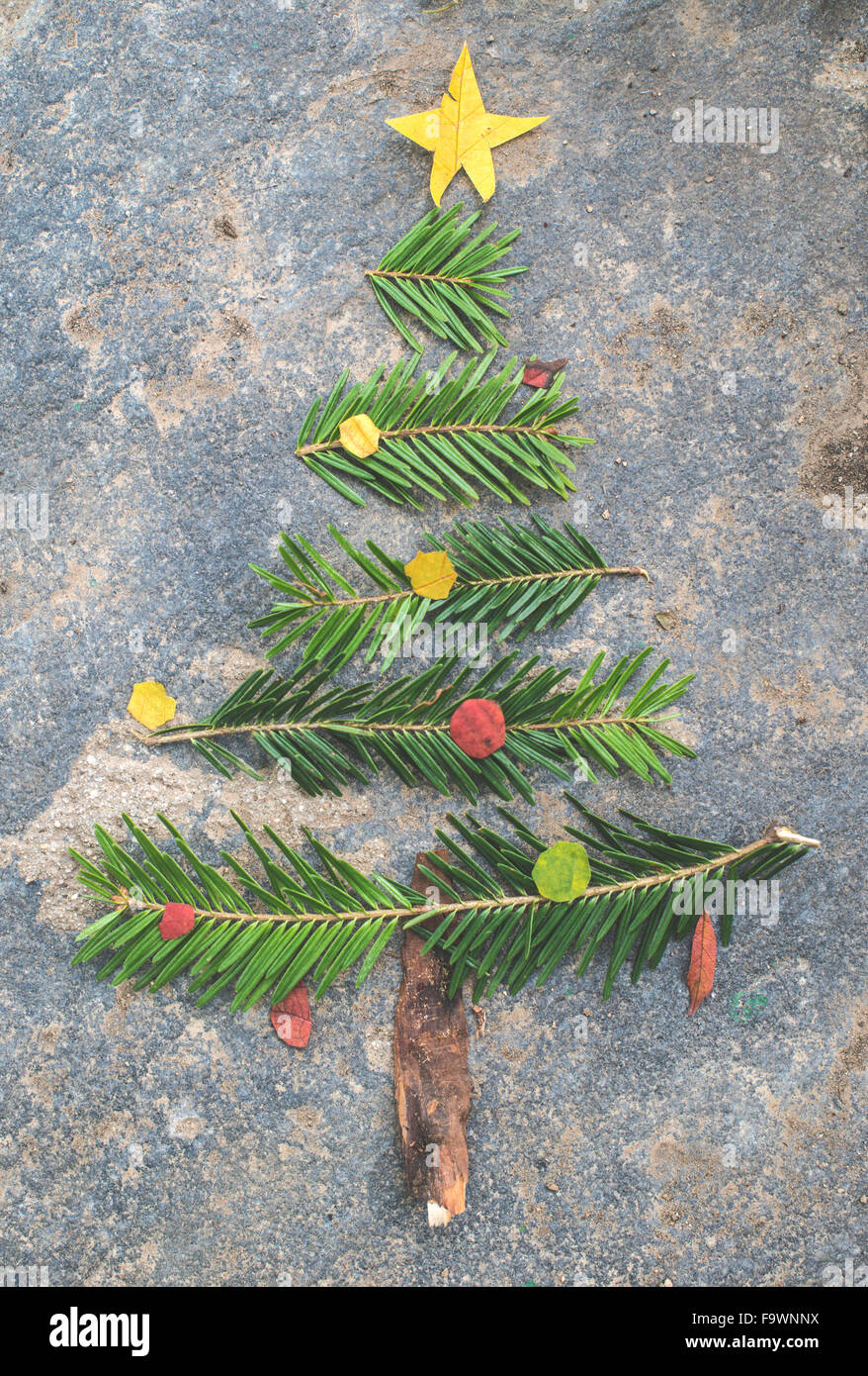 Pieces of fir branch, leaves and bark building shape of a Christmas tree - Stock Image