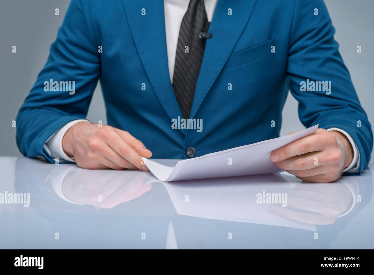 Professional newscaster reading his papers. - Stock Image