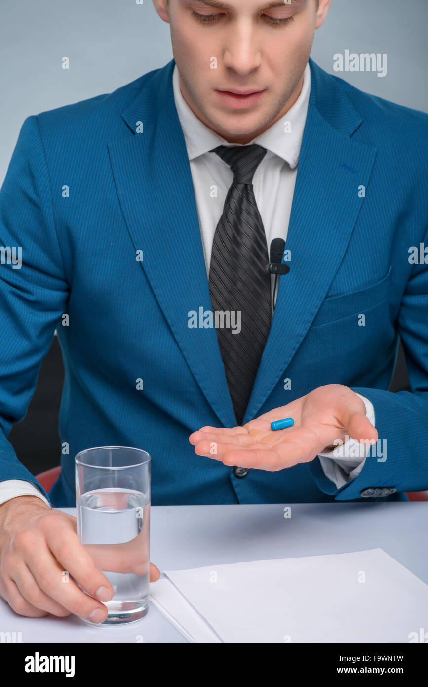 Professional newscaster is about to take a medicine. - Stock Image