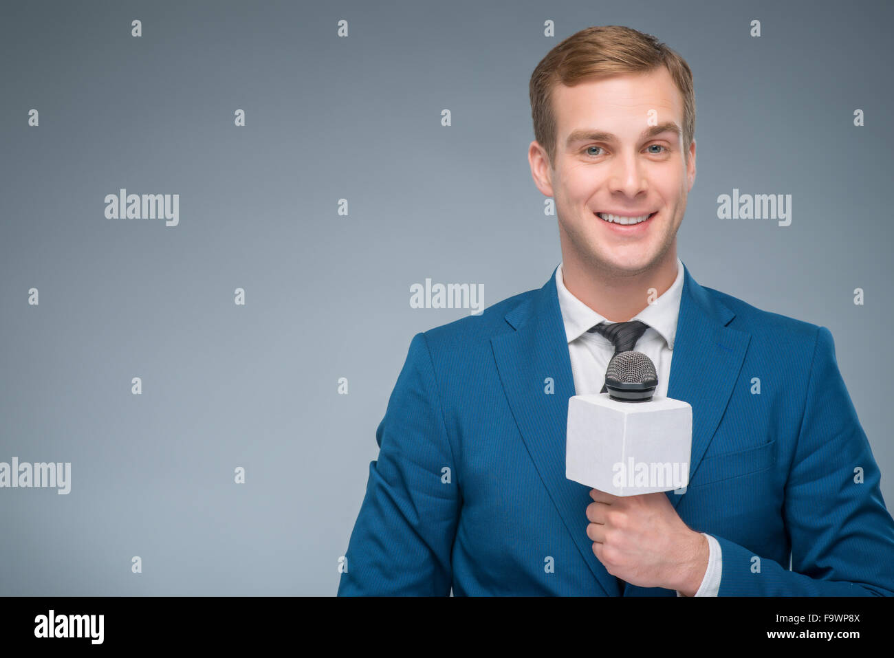 Smiling newsman holding a microphone. - Stock Image