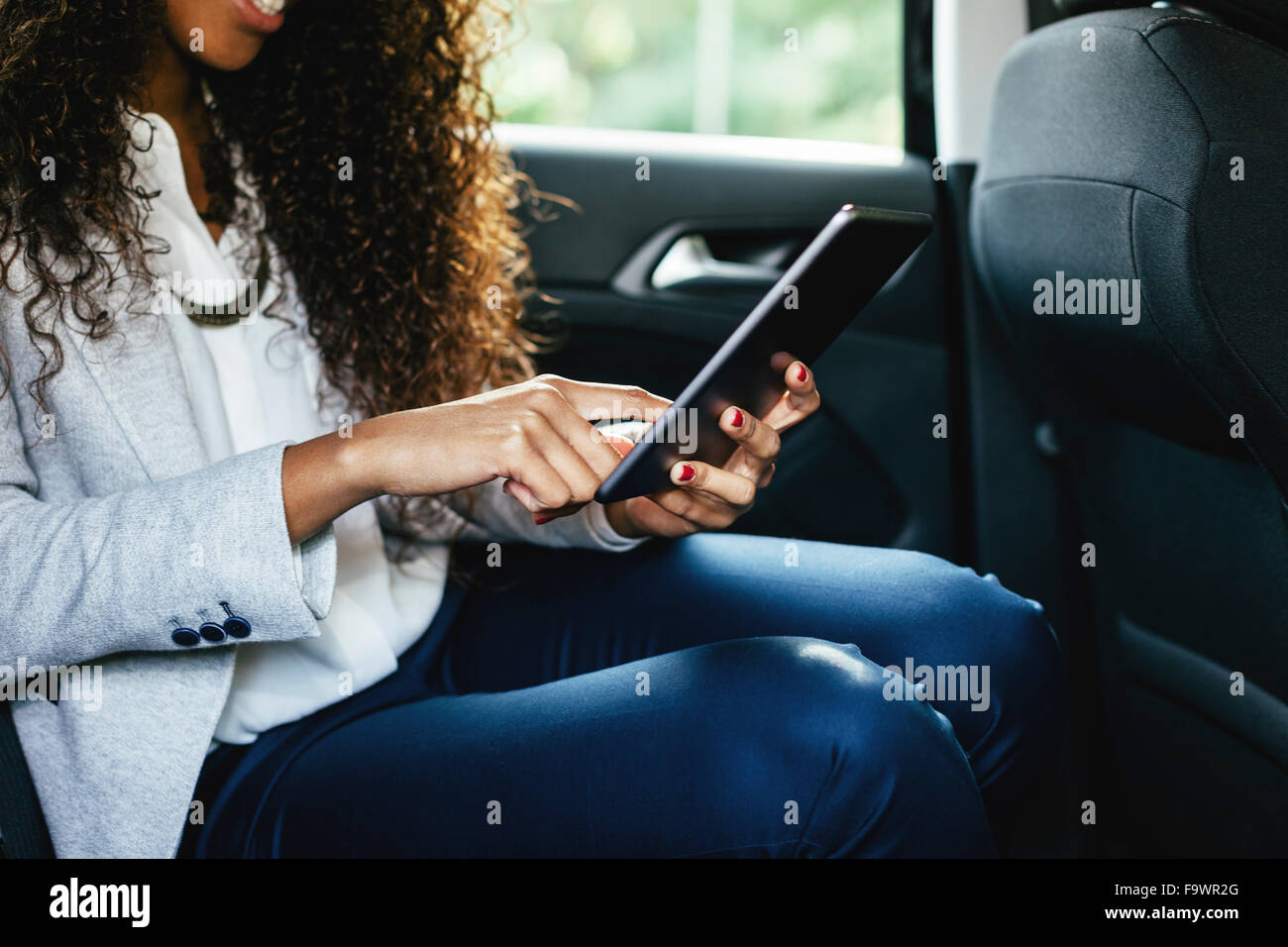 Young woman sitting on back seat of a car using mini tablet, close-up - Stock Image