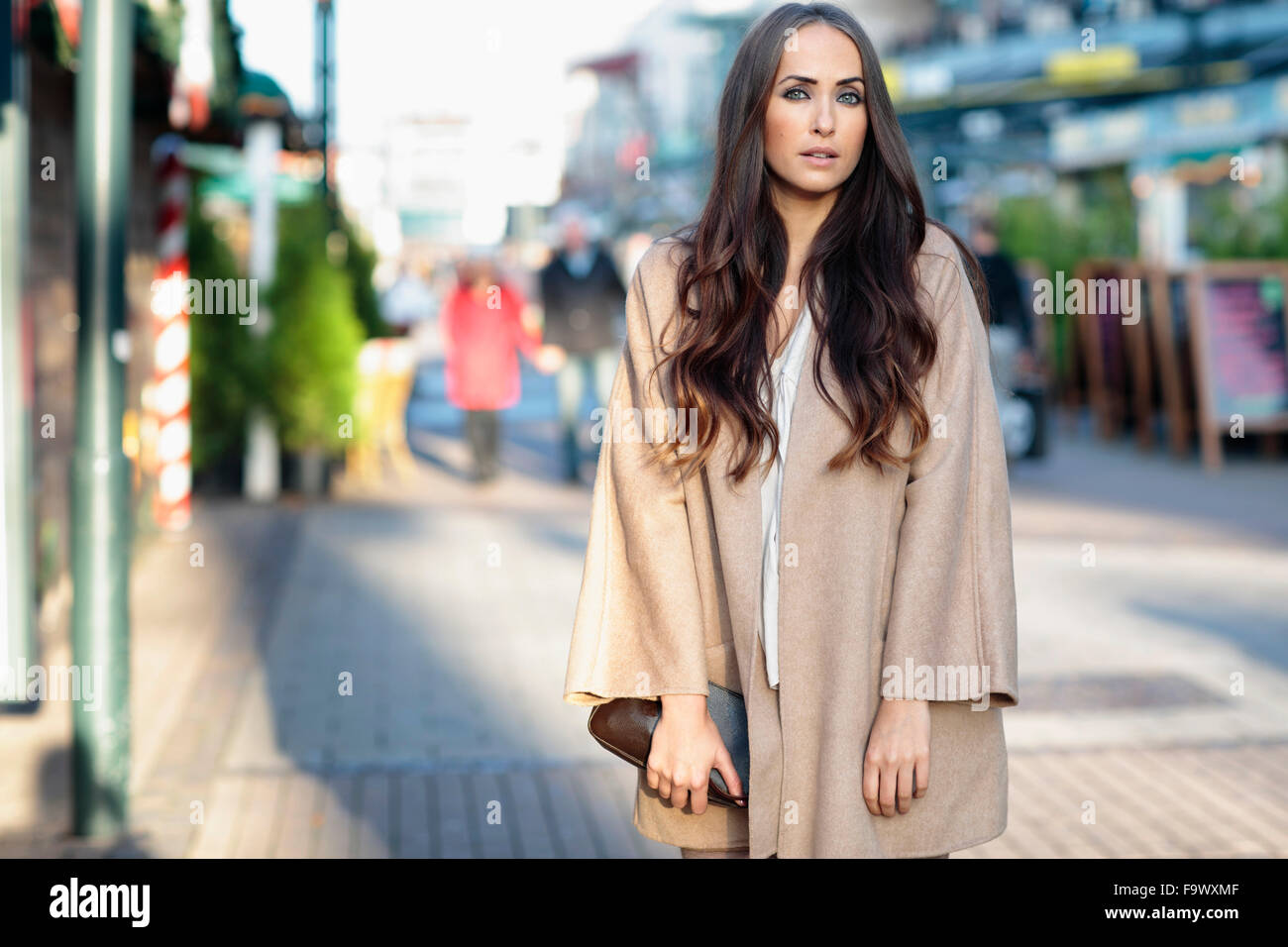 78f53cbab772c Portrait of young woman with long brown hair wearing light brown coat