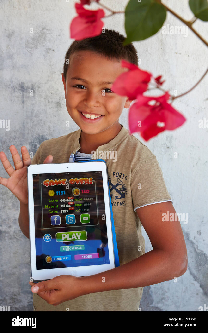 8-year-old boy using a digital tablet. - Stock Image