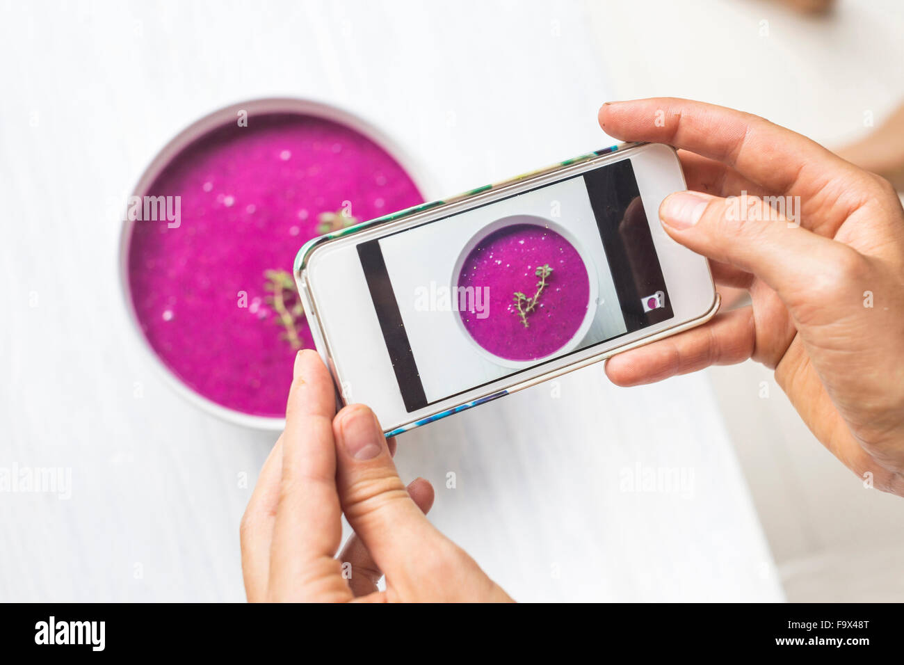 Woman taking a photo of dragon fruit smoothie with her smartphone, close-up Stock Photo