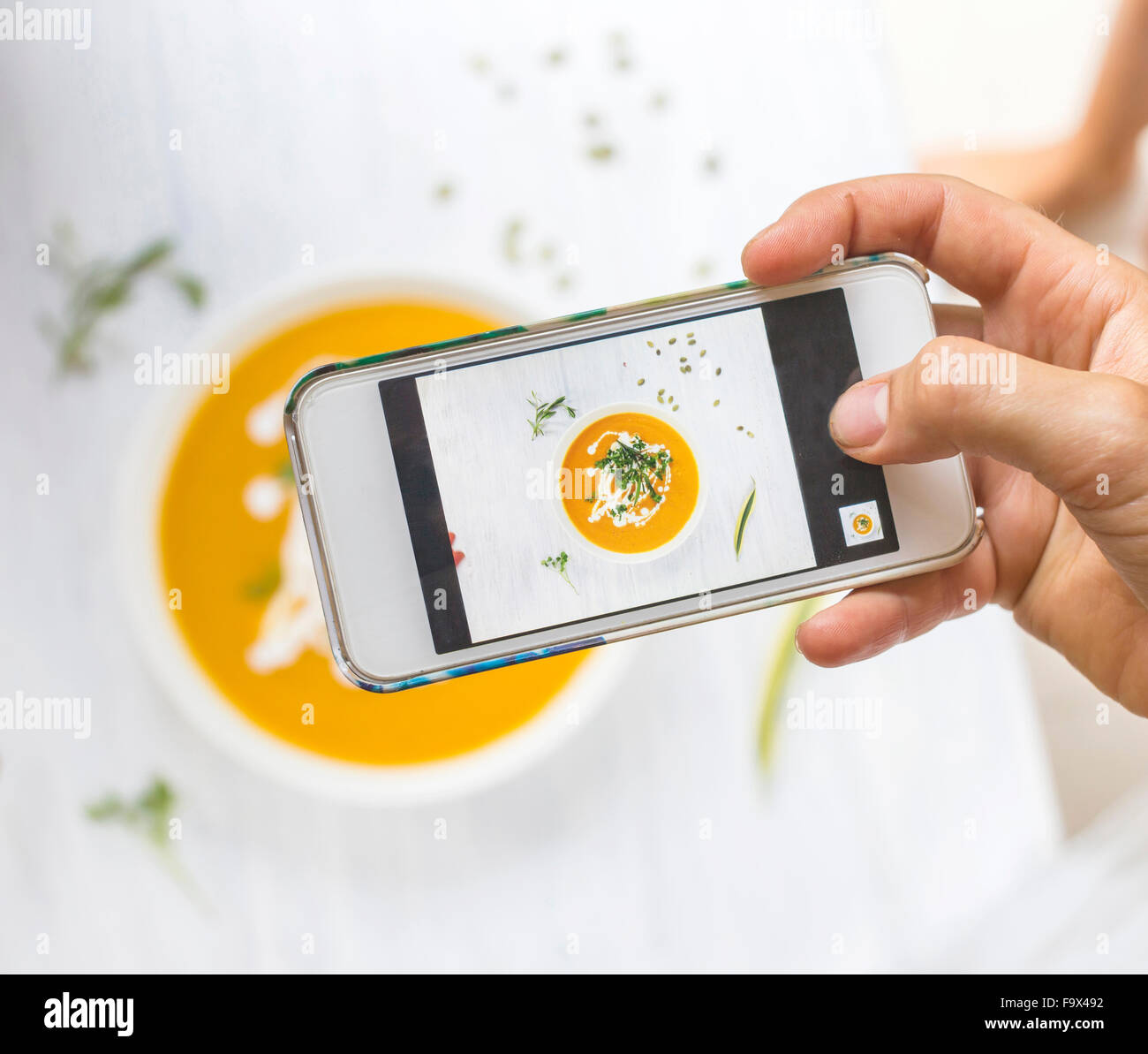 Woman taking a photo of carrot pumpkin soup with her smartphone, close-up - Stock Image