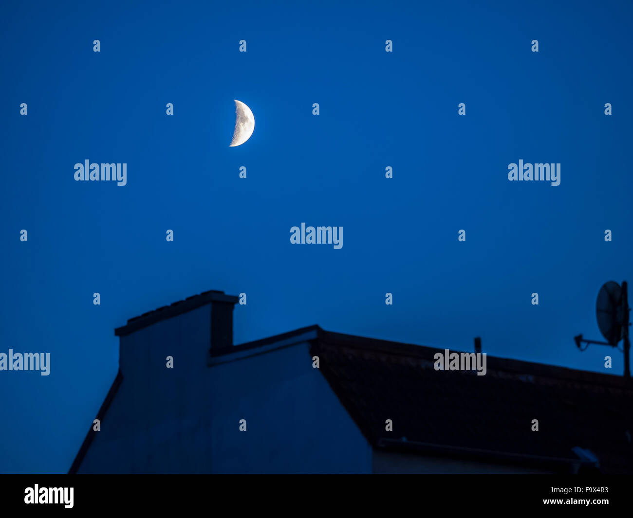 Germany, Hamburg, Half moon over roof top at blue hour - Stock Image
