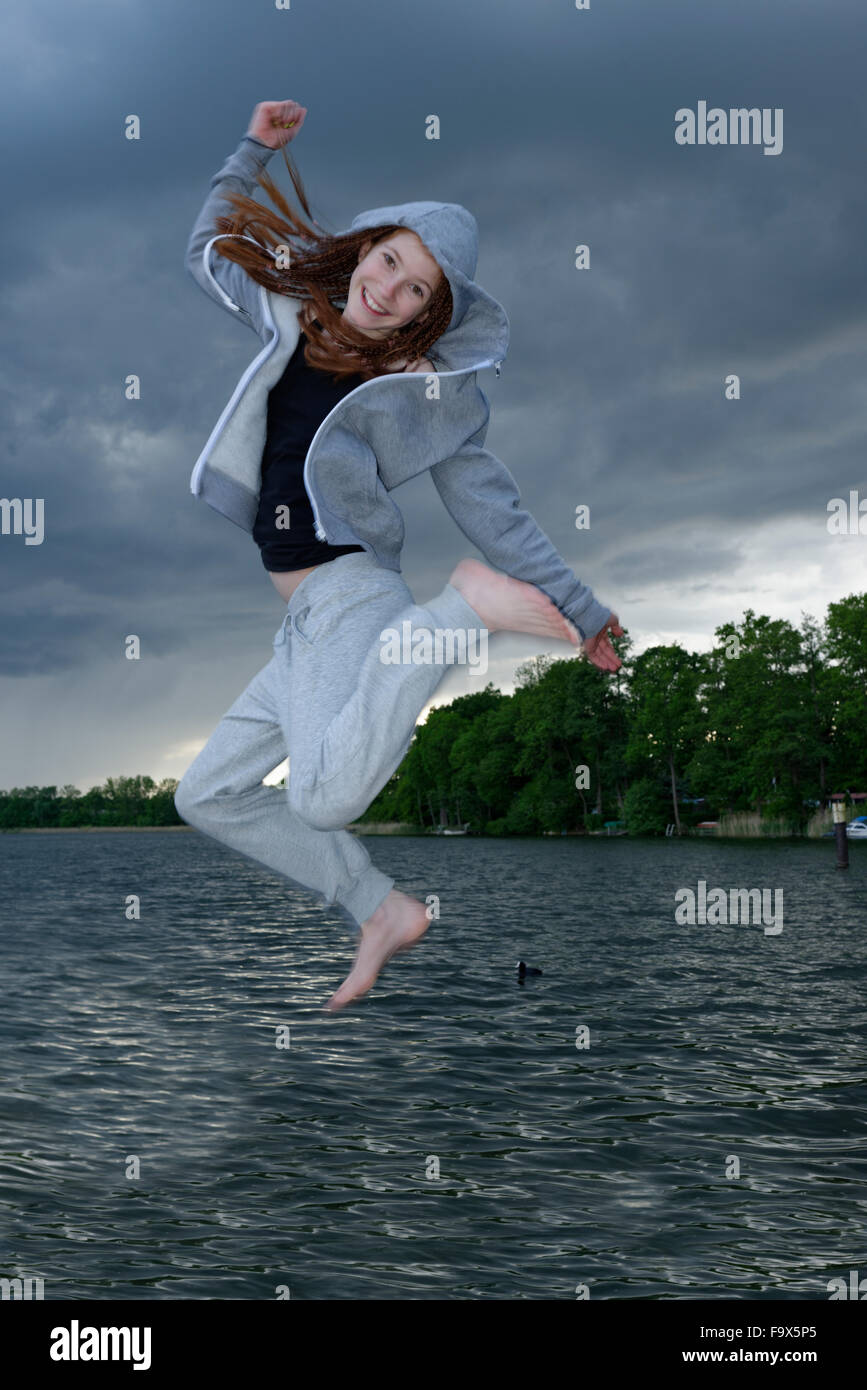 Girl jumping, lake in the background - Stock Image