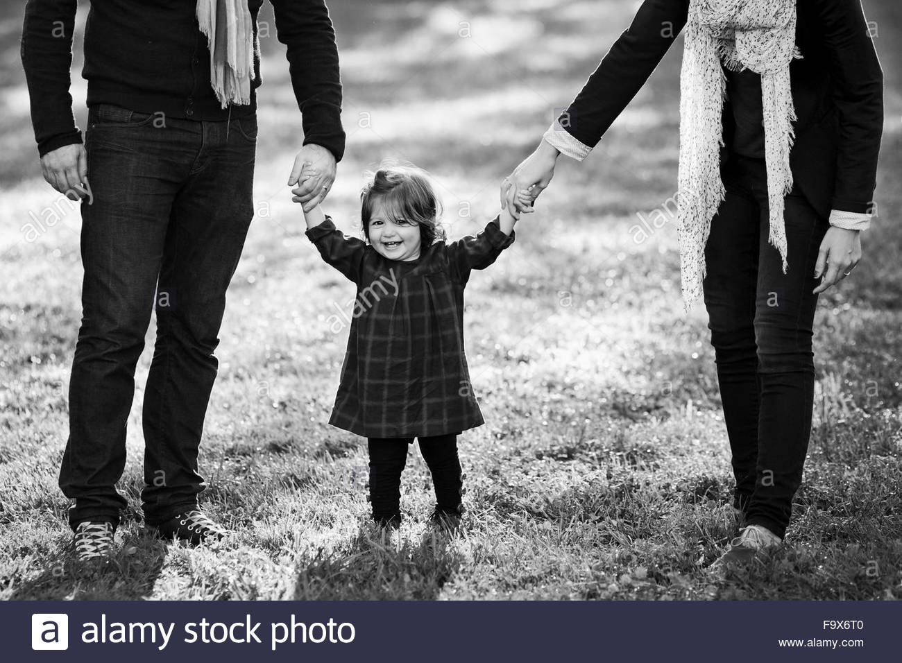 Mother and father holding hands of smiling baby girl - Stock Image