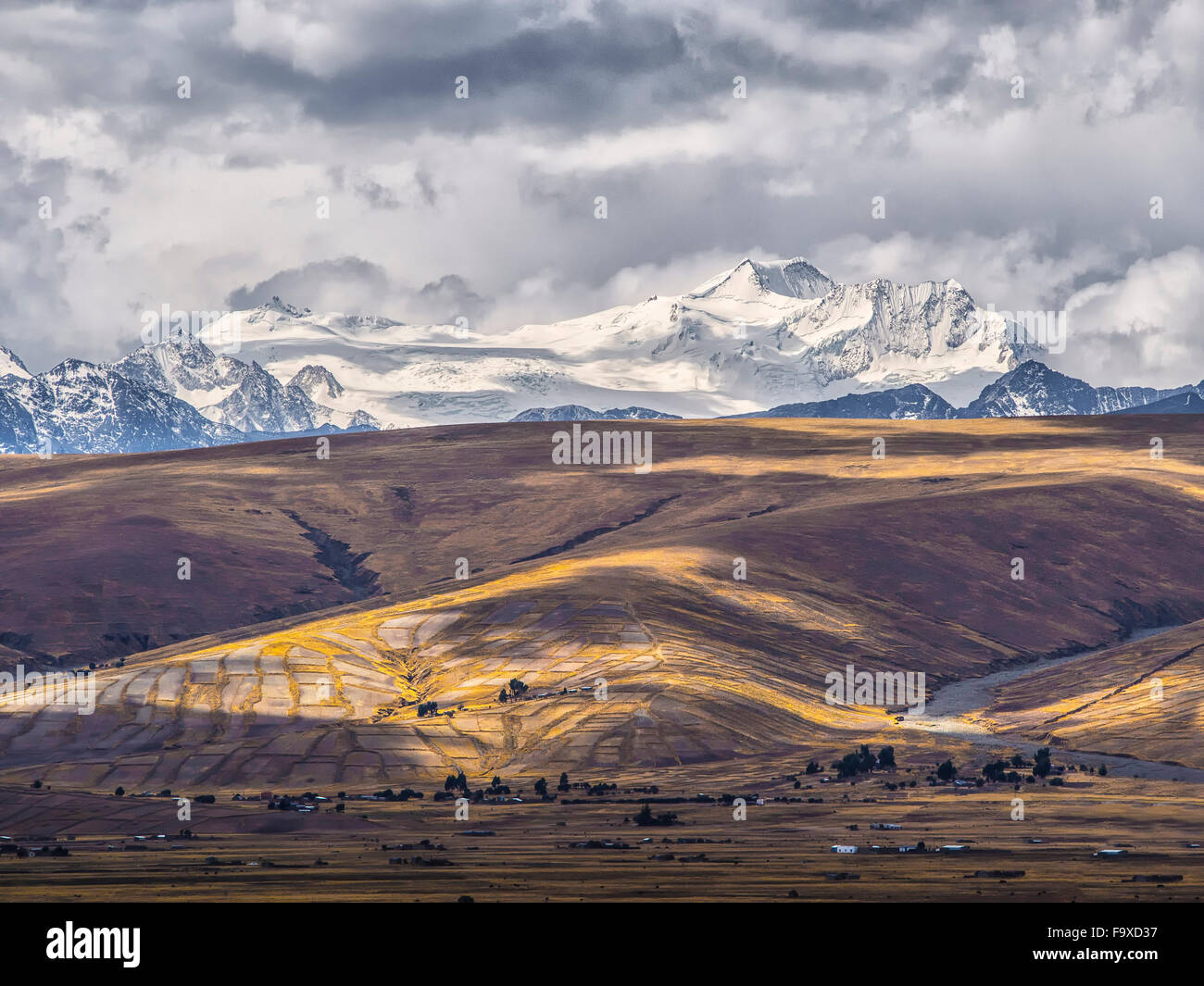 Bolivia, La Paz district, Altiplano, Rays of light between the clouds on the peaks of the Cordillera Real mountain - Stock Image