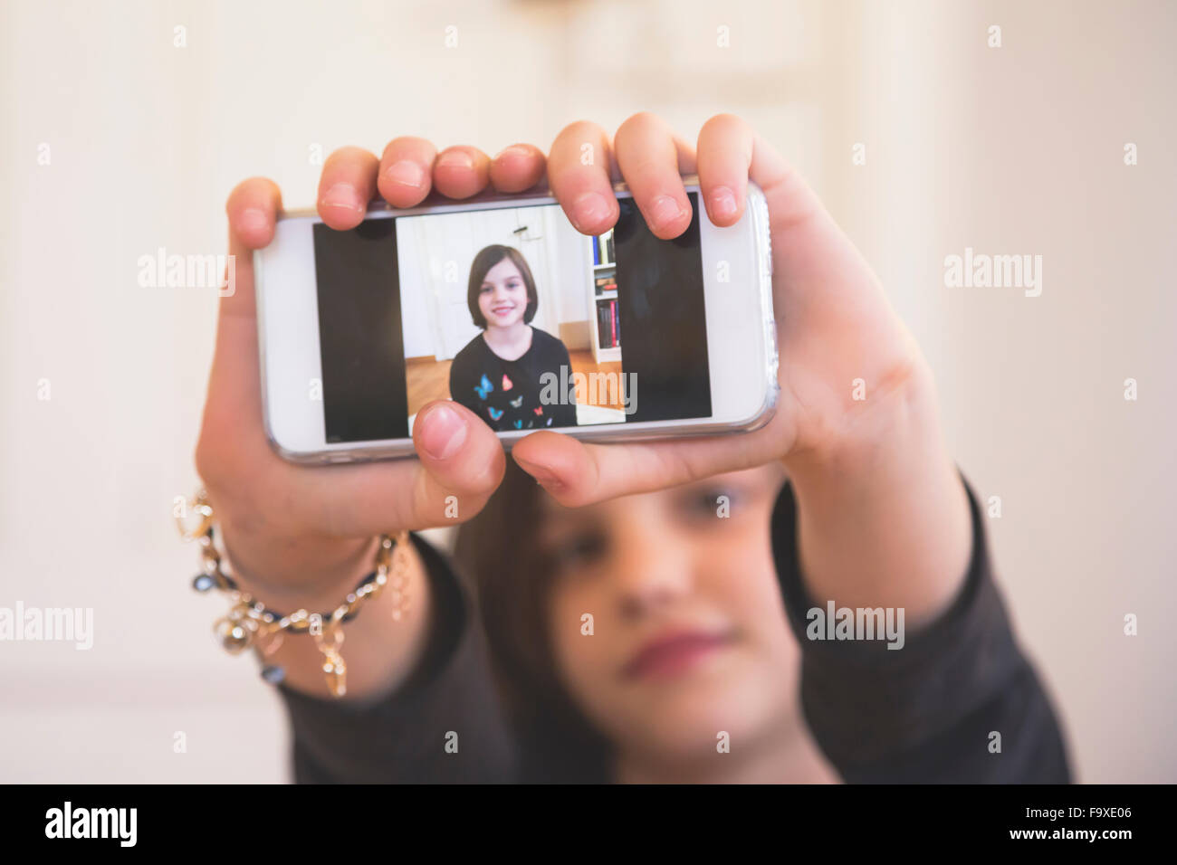 Hands of girl showing smartphone with photography of herself - Stock Image