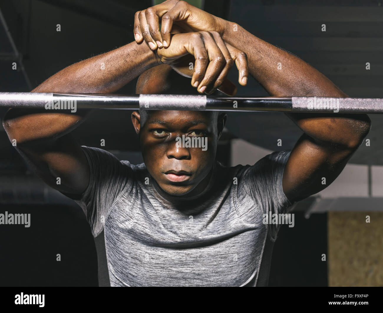 Portrait of physical athlete resting on barbell in gym - Stock Image
