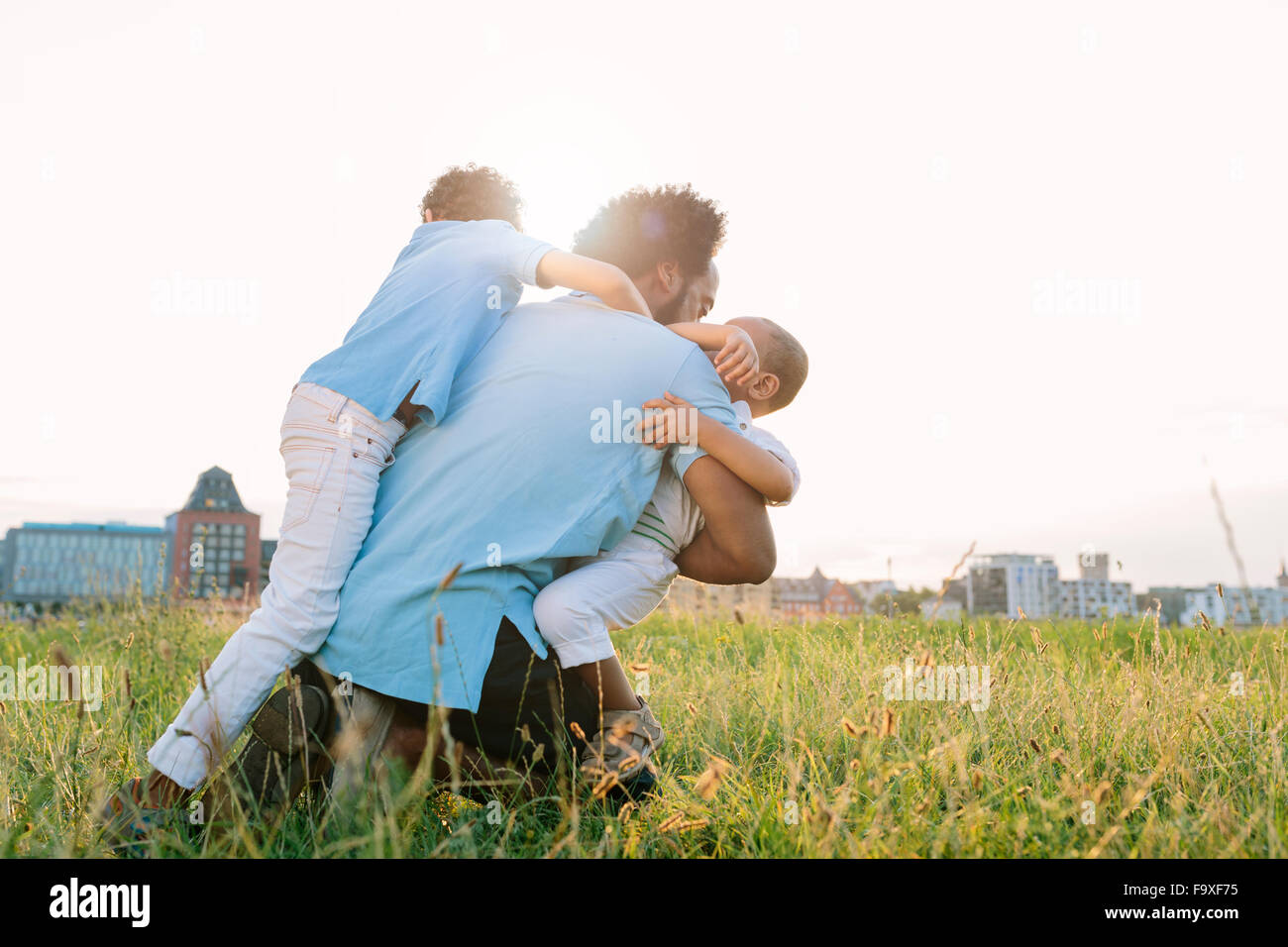 Germany, Cologne, playful father with two sons in field - Stock Image