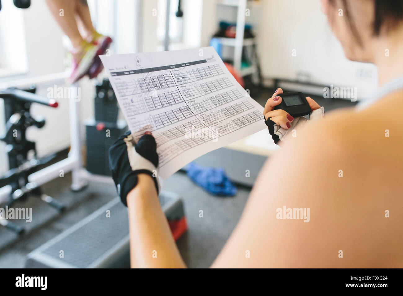 Woman taking the time while athlete doing pull-ups in gym Stock Photo