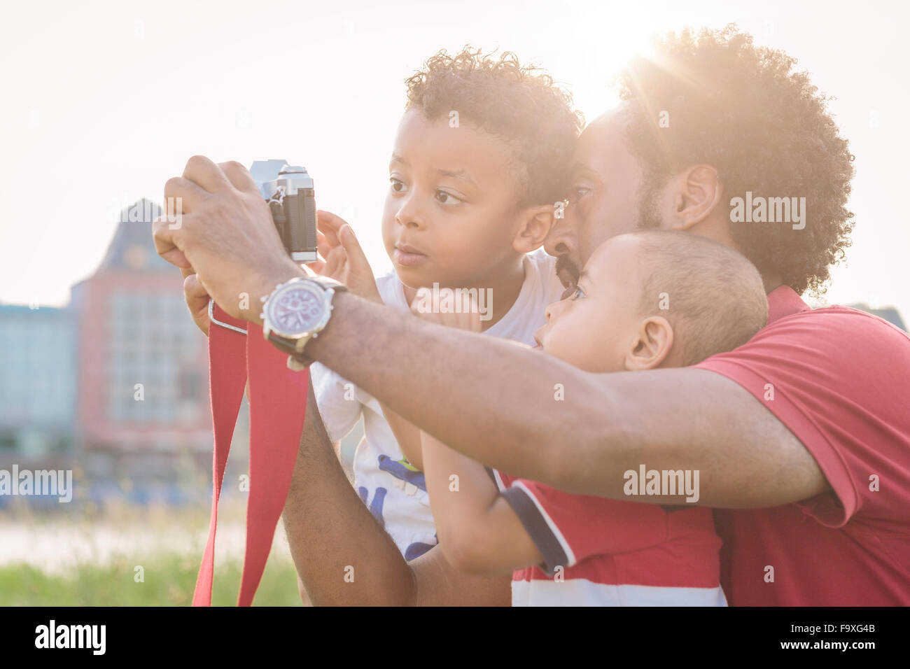 Father explaining camera to his sons outdoors - Stock Image