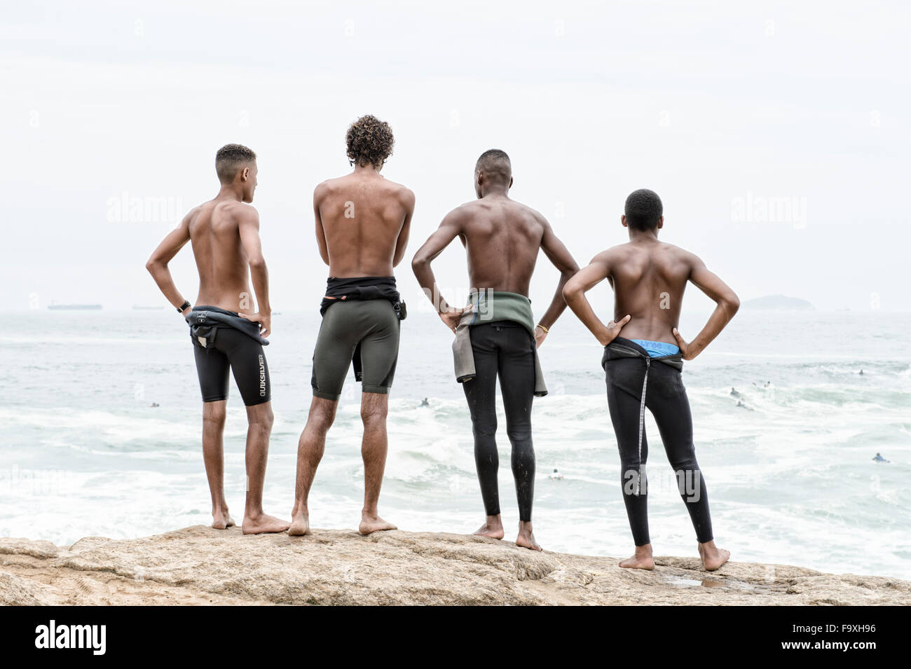 RIO DE JANEIRO, BRAZIL - OCTOBER 22, 2015: Brazilian surfers in wetsuits look at incoming waves at Praia do Diabo - Stock Image