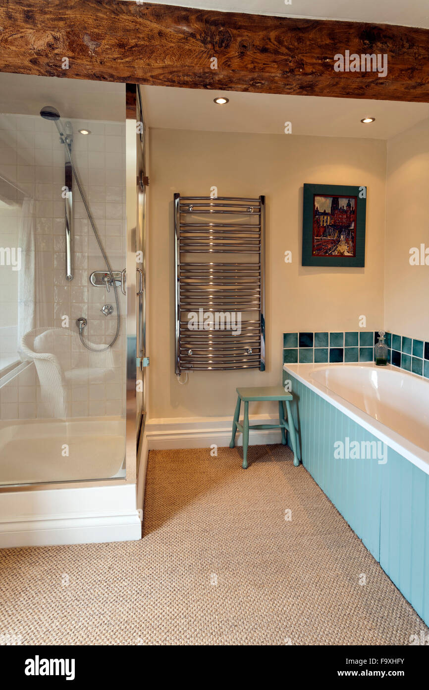 A stylish bathroom with a glossy chrome shower cubicle and radiator. - Stock Image