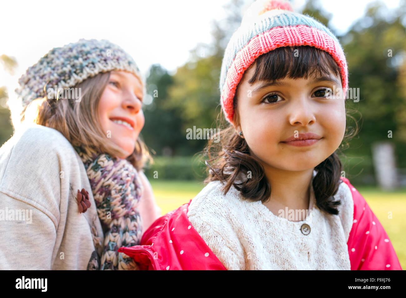 Two little girls wearing woolly hats - Stock Image