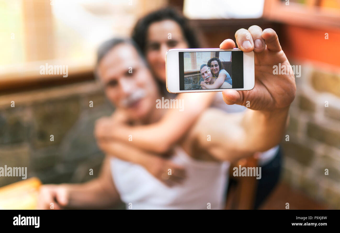 Photo of couple taking a selfie on display of smartphone - Stock Image