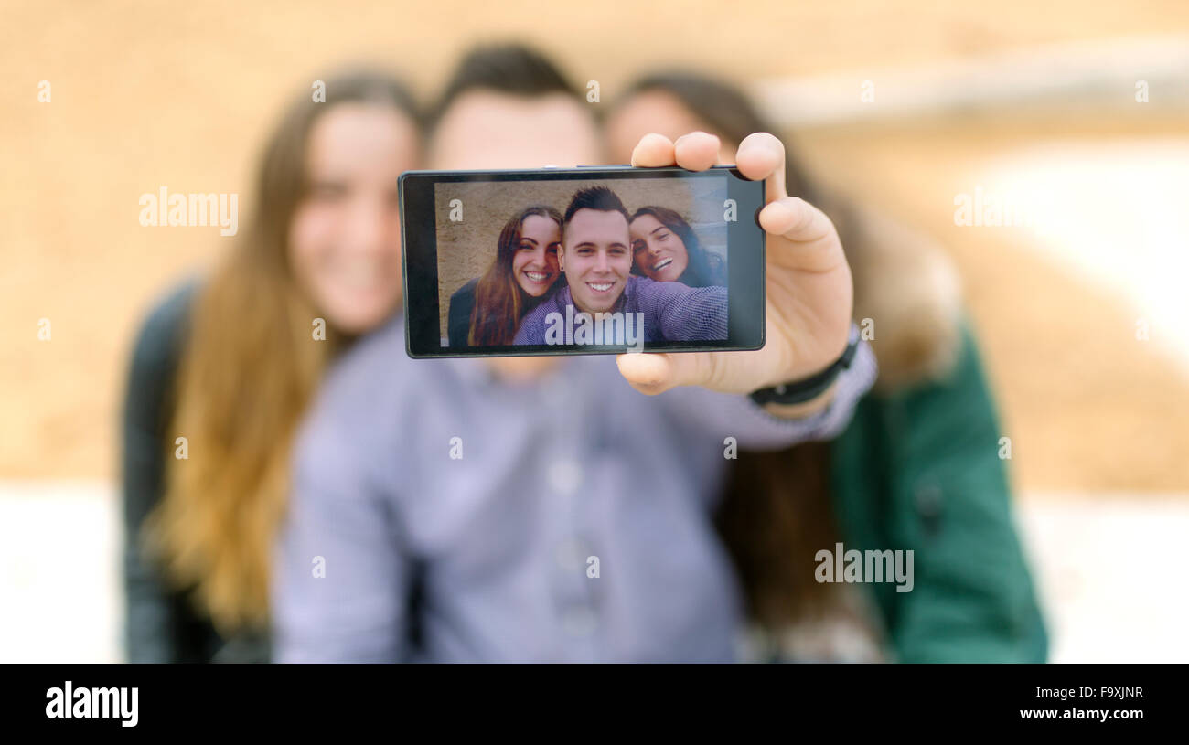 Selfie of smiling friends on display of smartphone - Stock Image
