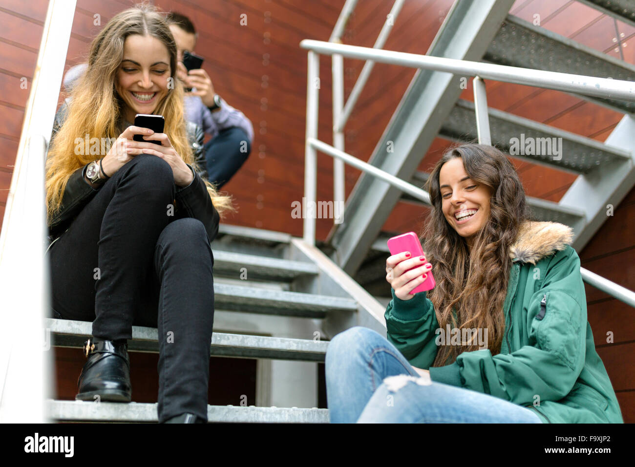 Three friends hanging around with cell phones oudoors - Stock Image