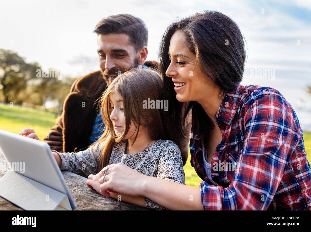 Happy parents with daughter using digital tablet outdoors - Stock Image