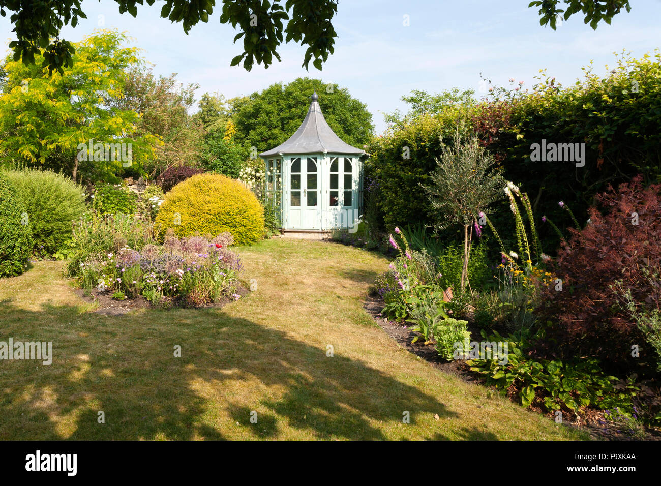 UK gardens. An octagonal painted summerhouse in a summer garden. - Stock Image