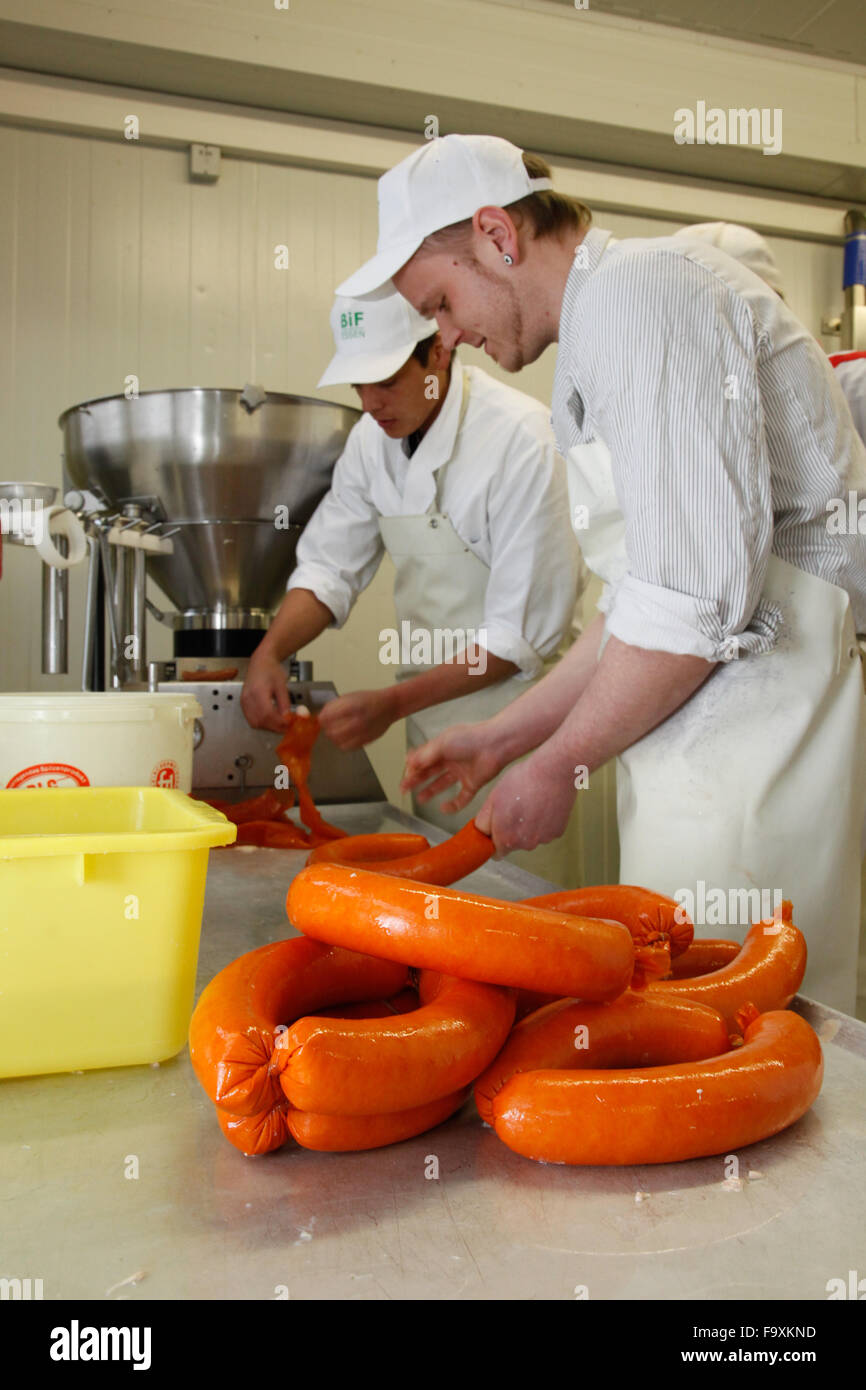 Butchers at the sausage machine making pork sausages. Stock Photo
