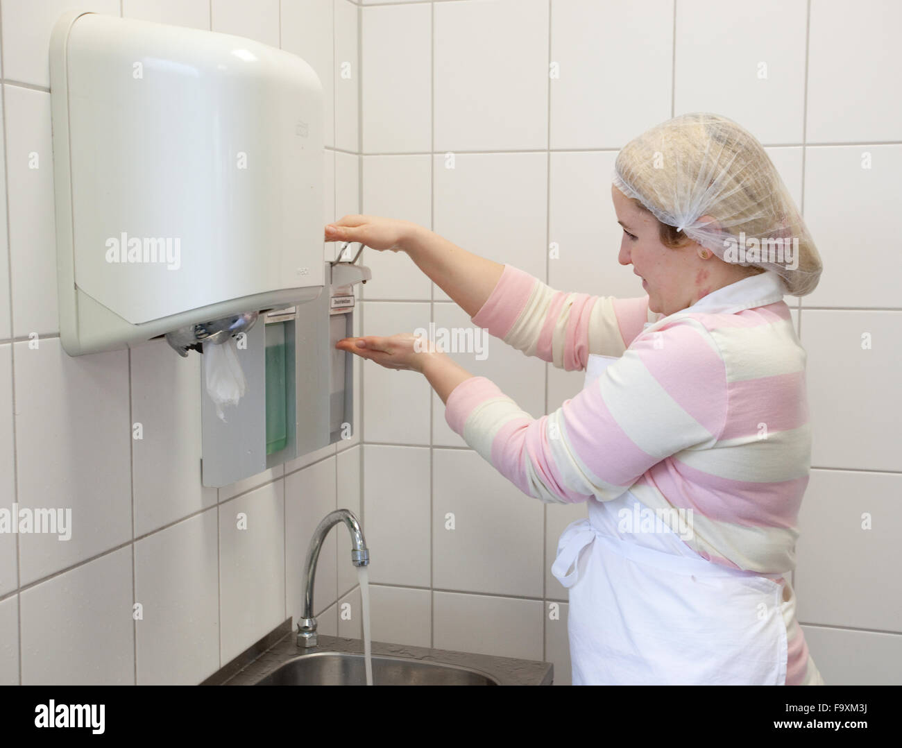 Larder cook  washes her hands. - Stock Image