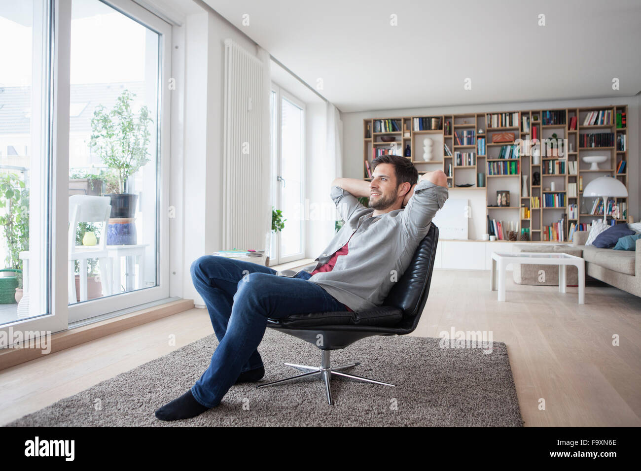 Smiling man at home sitting in armchair with hands behind head - Stock Image