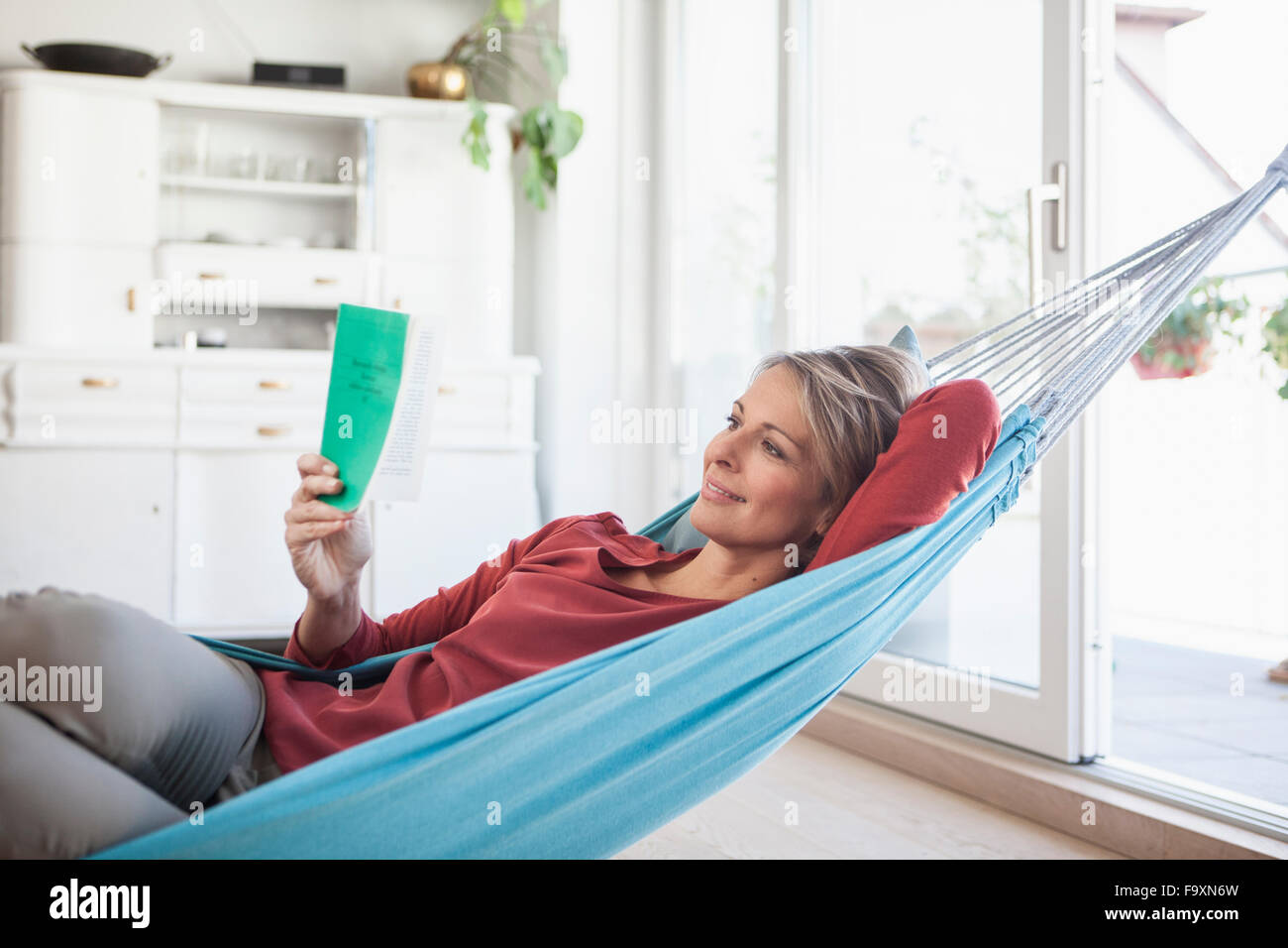 Smiling woman at home lying in hammock reading book - Stock Image