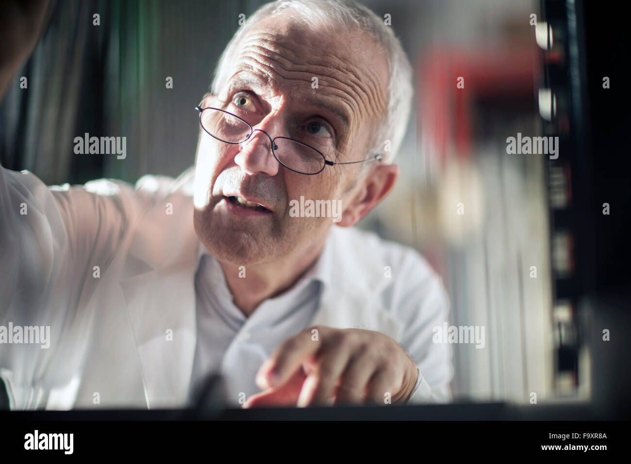 Portrait of man controlling device - Stock Image