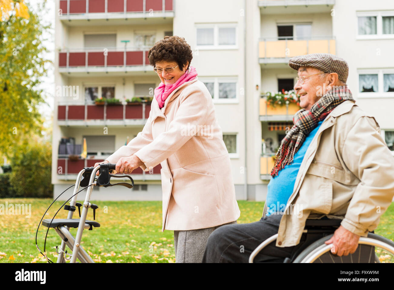 Senior woman with wheeled walker and senior man in wheelchair outdoors in autumn - Stock Image
