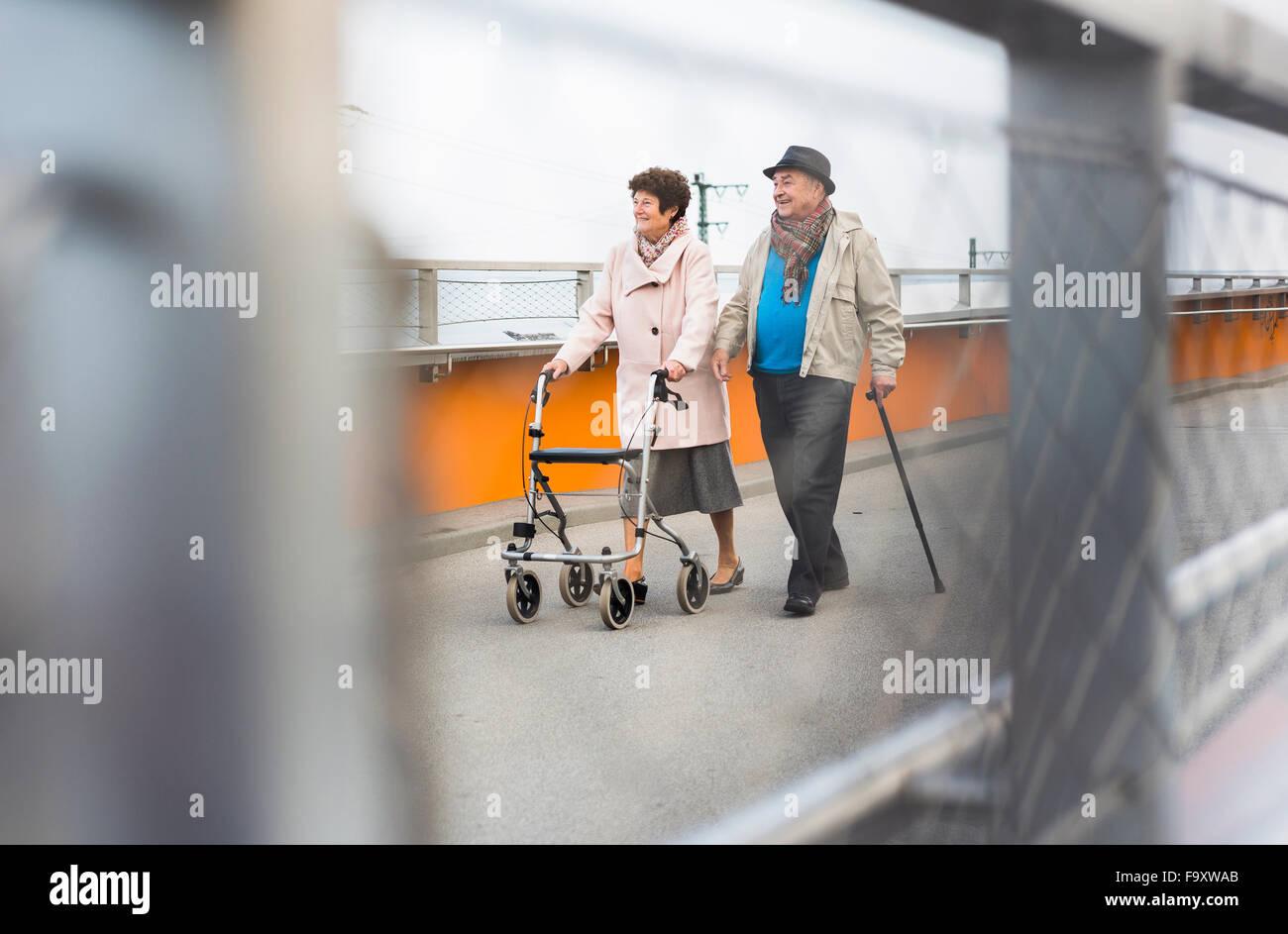 Senior couple walking with walking stick and wheeled walker - Stock Image