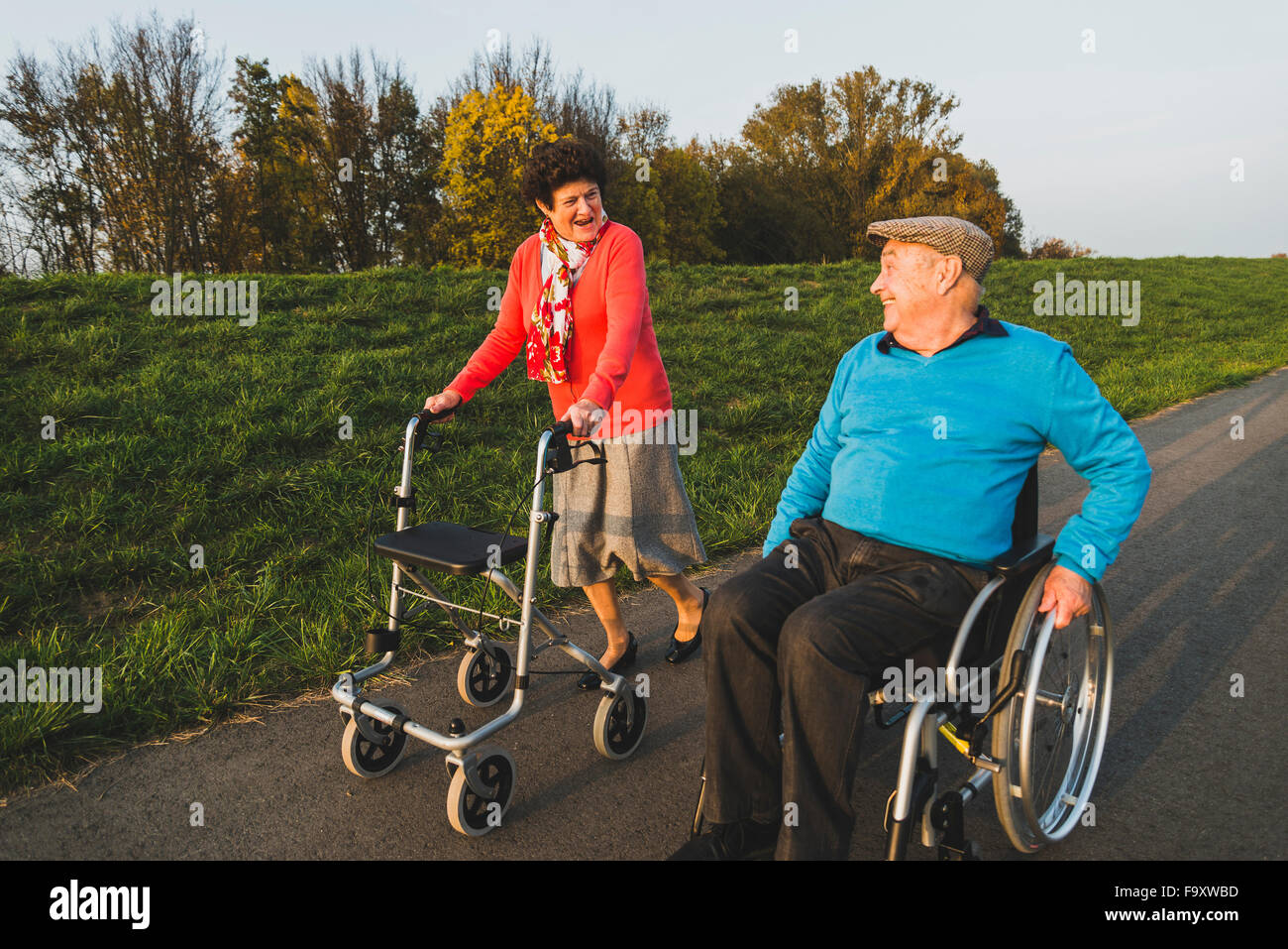 Smiling senior couple with wheelchair and wheeled walker on a path - Stock Image