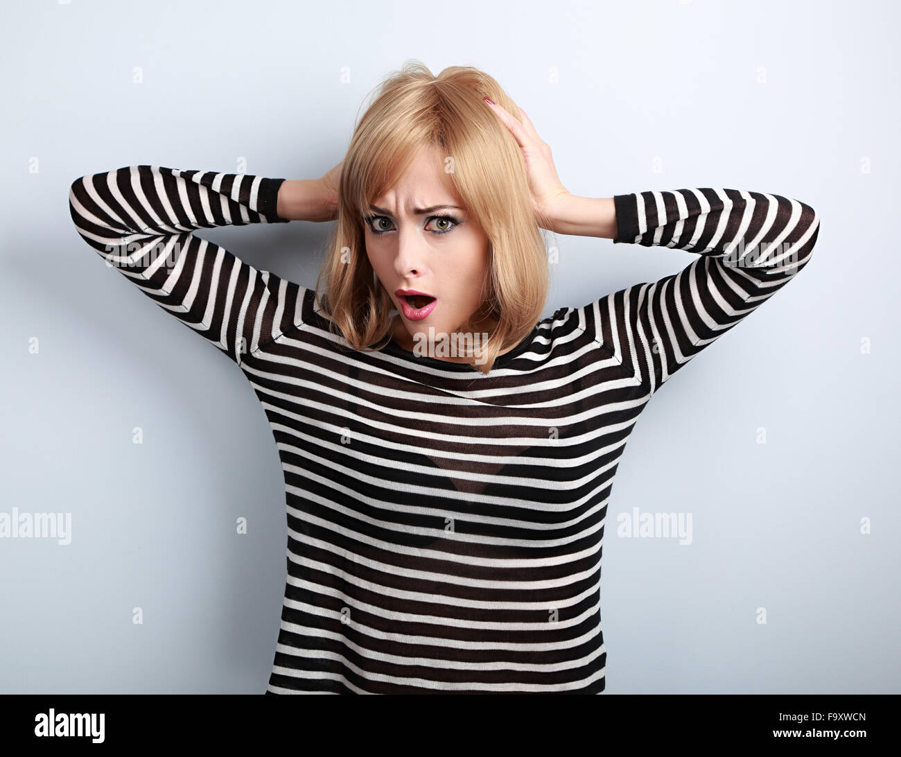 Confused young woman with surprising big eyes holding hand hair. Stress concept on blue background - Stock Image