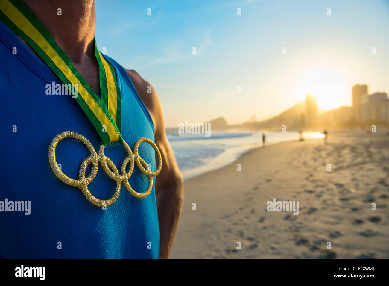 RIO DE JANEIRO, BRAZIL - OCTOBER 30, 2015: Athlete wearing Olympic rings gold medal stands at a sunset view of Copacabana - Stock Image