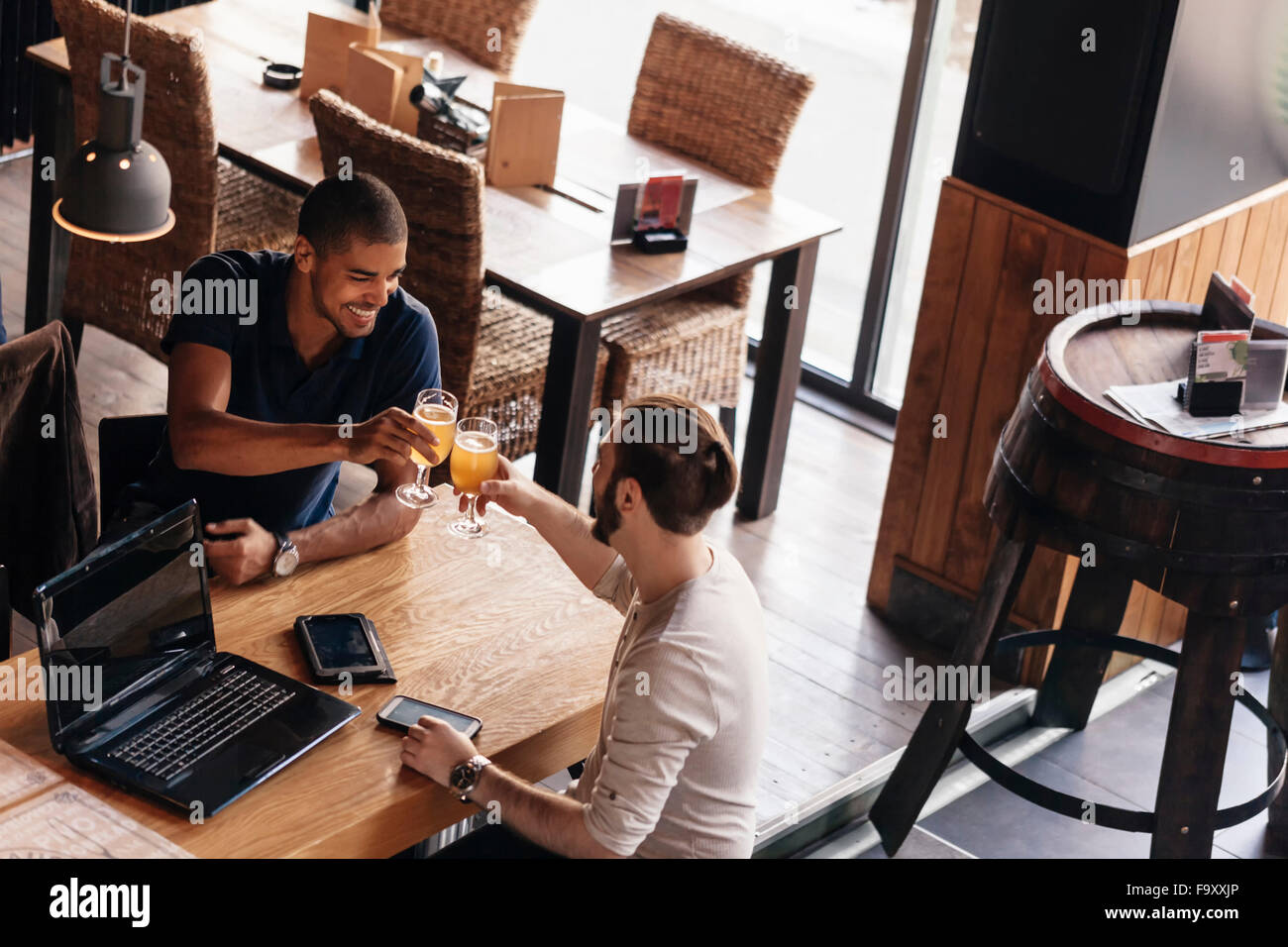 Two men with laptop and portable devices in a bar clinking beer glasses - Stock Image