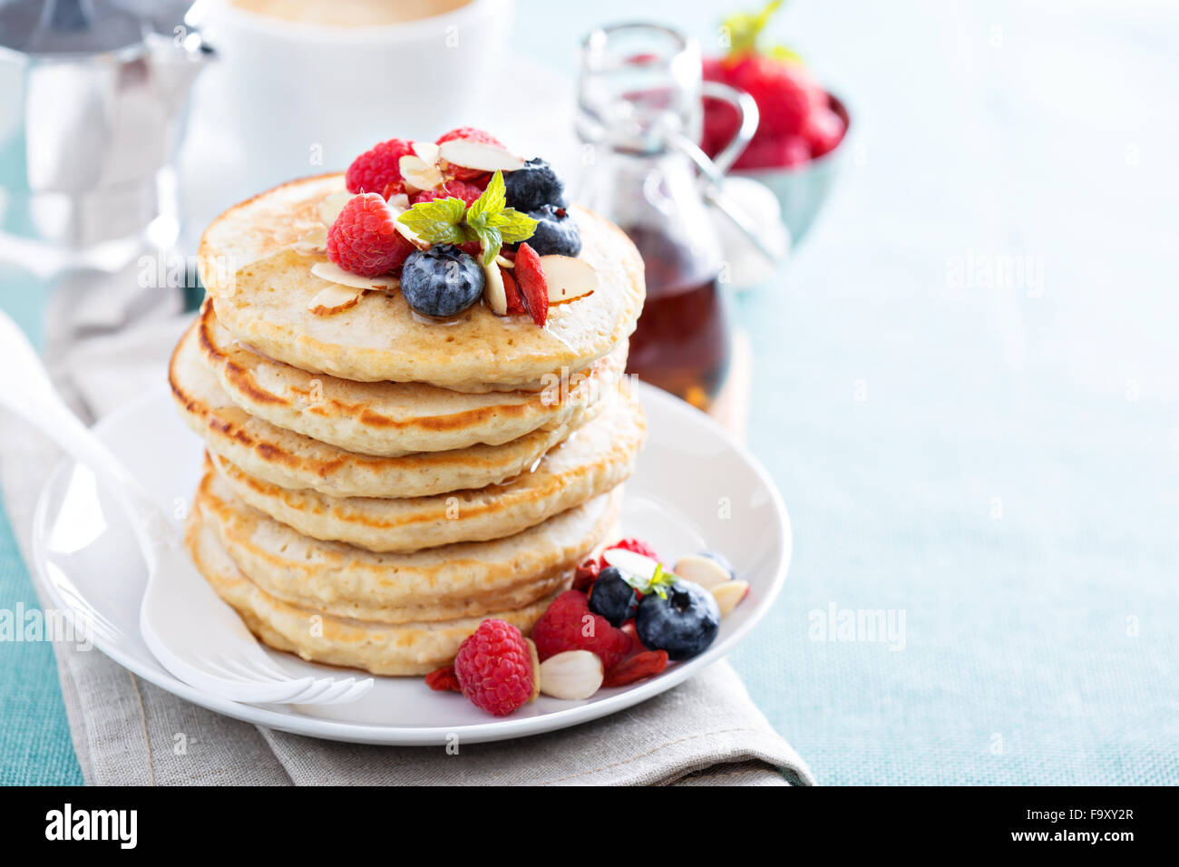 Fluffy oatmeal pancakes stack with fresh berries, coffee and syrup - Stock Image