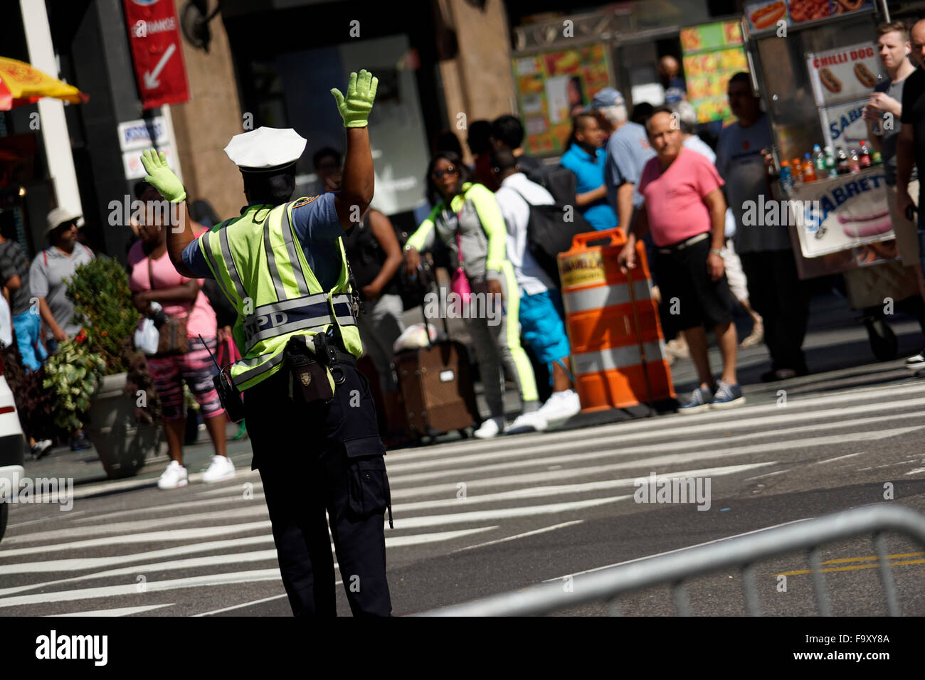Police woman directing traffic near Herald Square in midtown Manhattan, New York City, USA - Stock Image