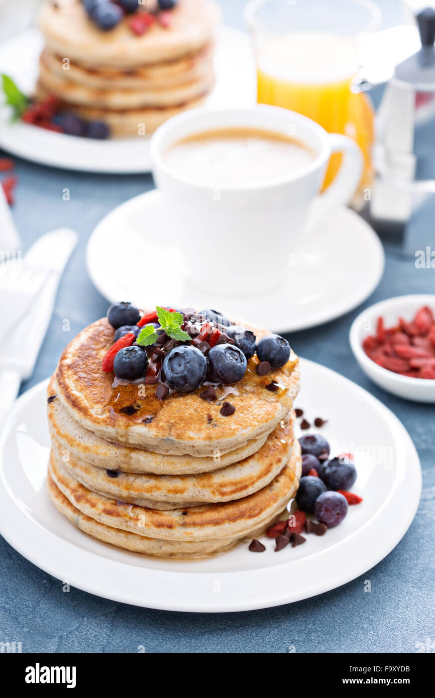 Fluffy chocolate chip pancakes on breakfast table - Stock Image