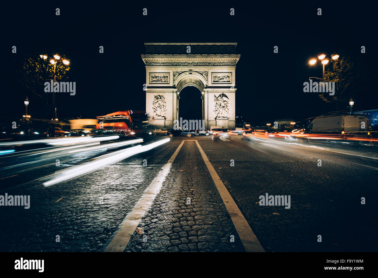 Traffic on Avenue des Champs-Élysées and the Arc de Triomphe at night in Paris, France. - Stock Image