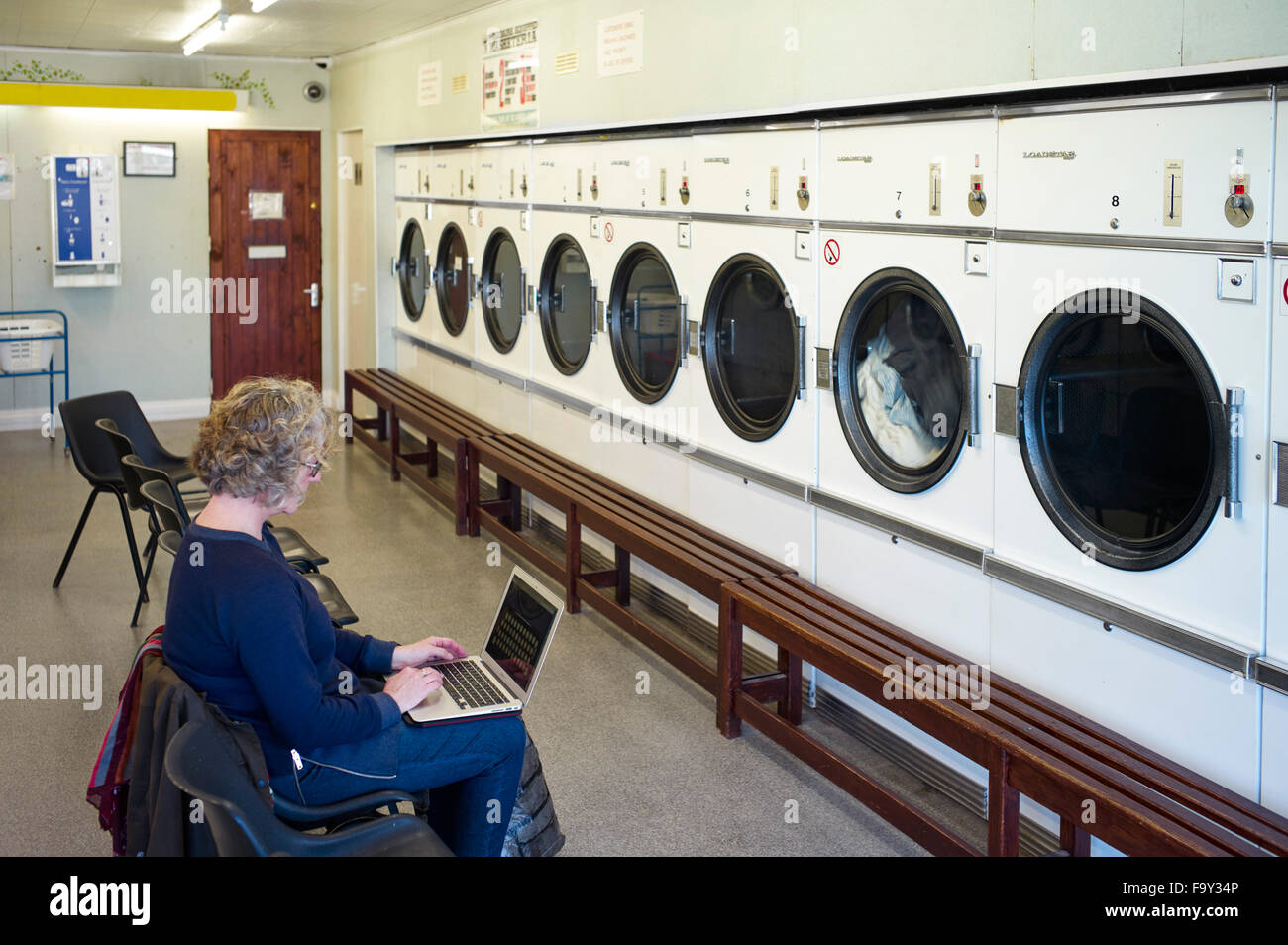 Woman on laptop in launderette - Stock Image