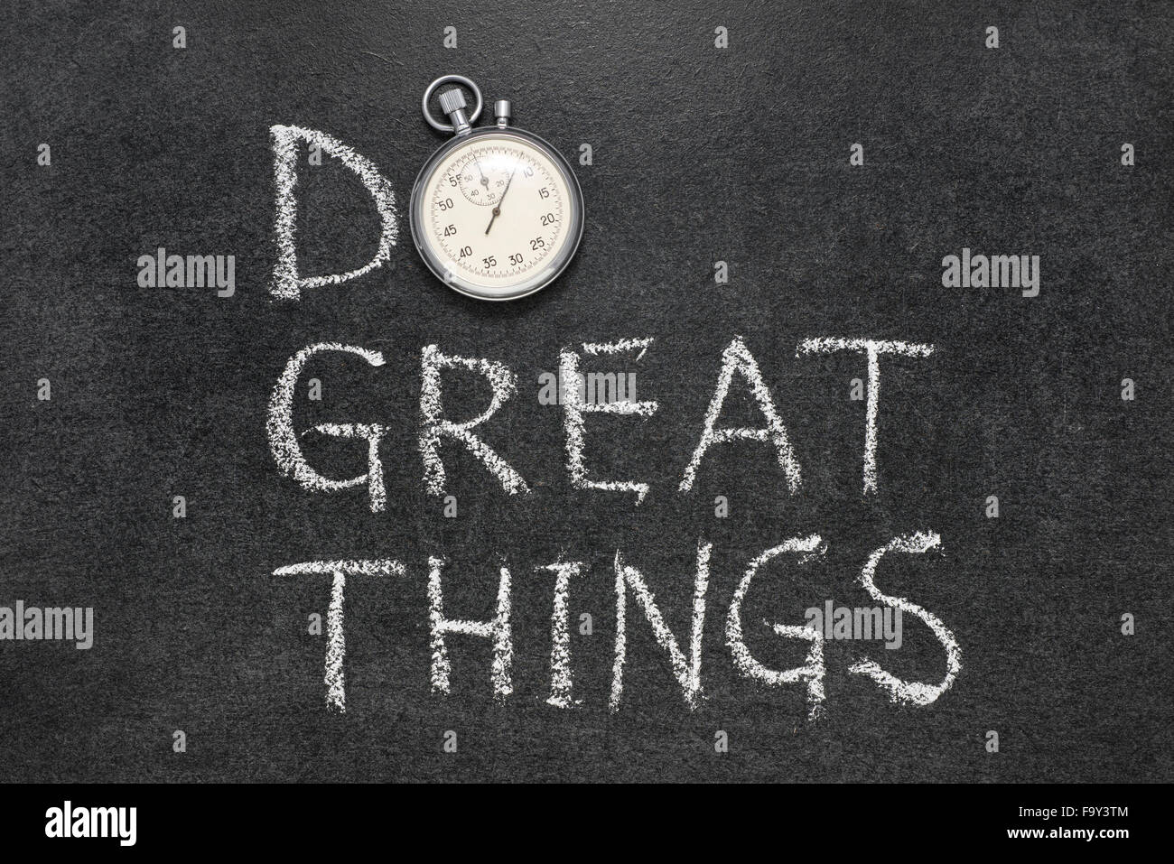 do great things phrase handwritten on chalkboard with vintage precise stopwatch used instead of O Stock Photo