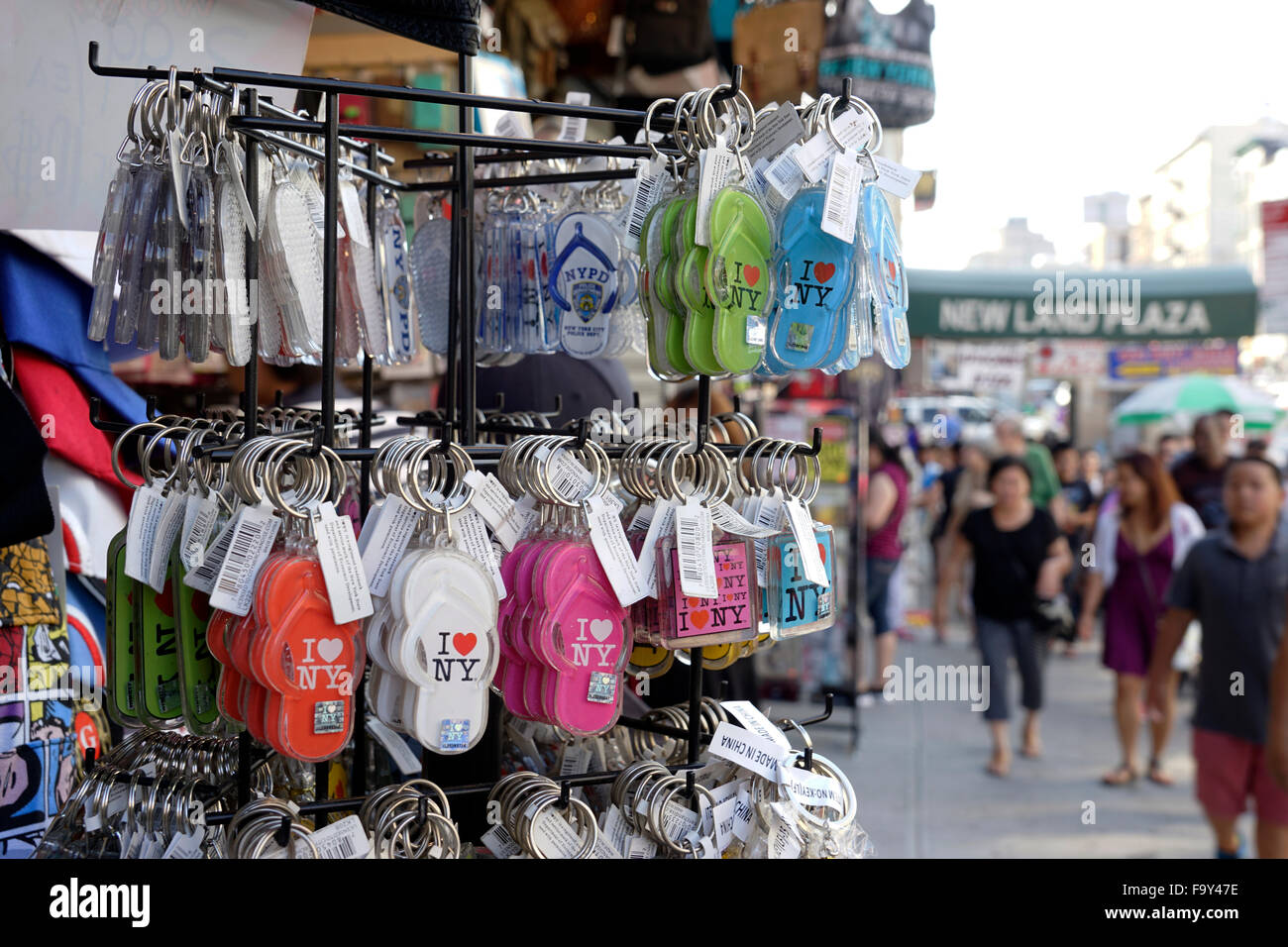 Souvenir vendor selling colorful flip flop key chain on Canal Street in New York City Chinatown, USA - Stock Image