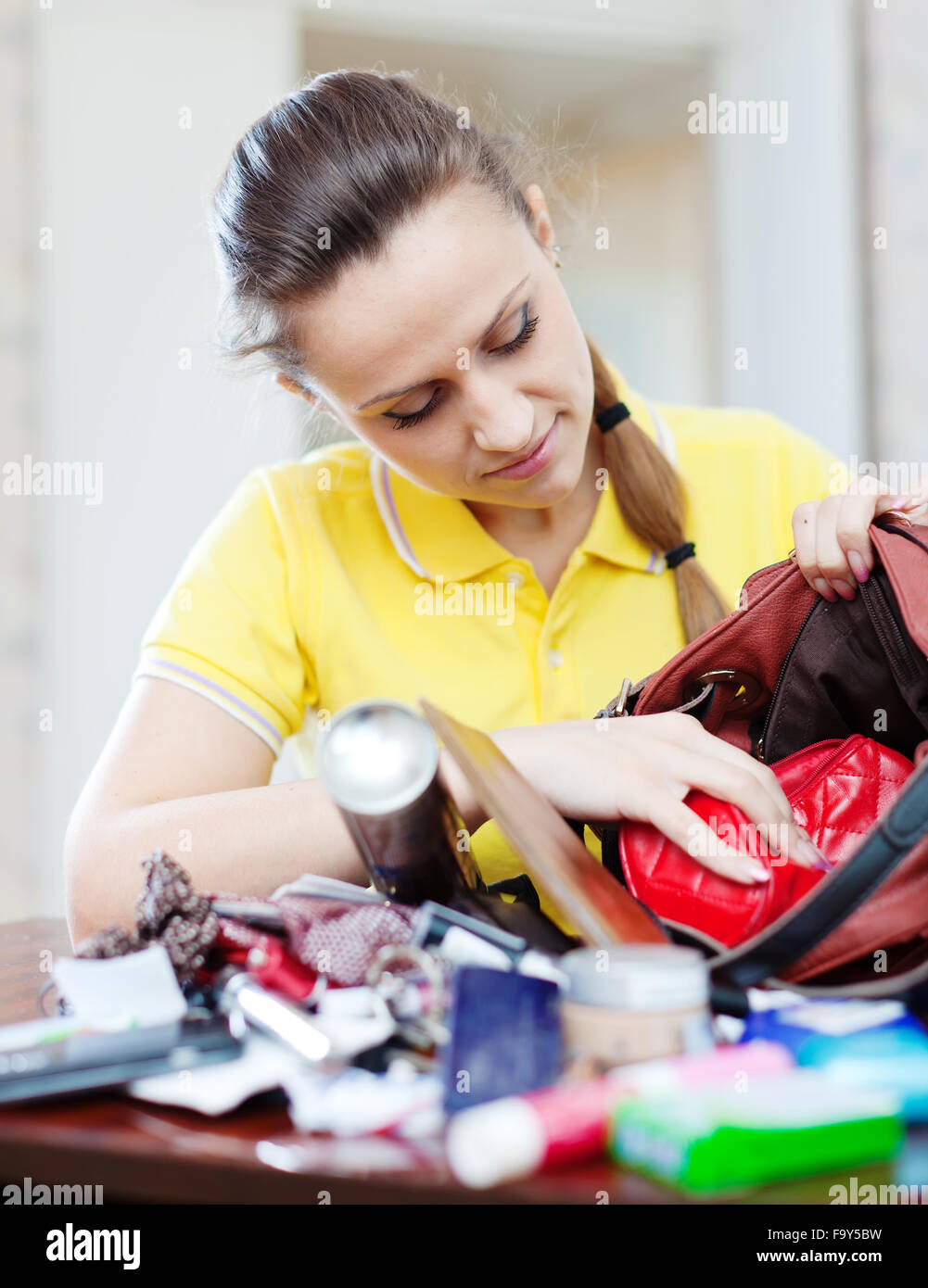 https://c8.alamy.com/comp/F9Y5BW/inconsiderate-woman-searching-something-in-handbag-at-home-F9Y5BW.jpg