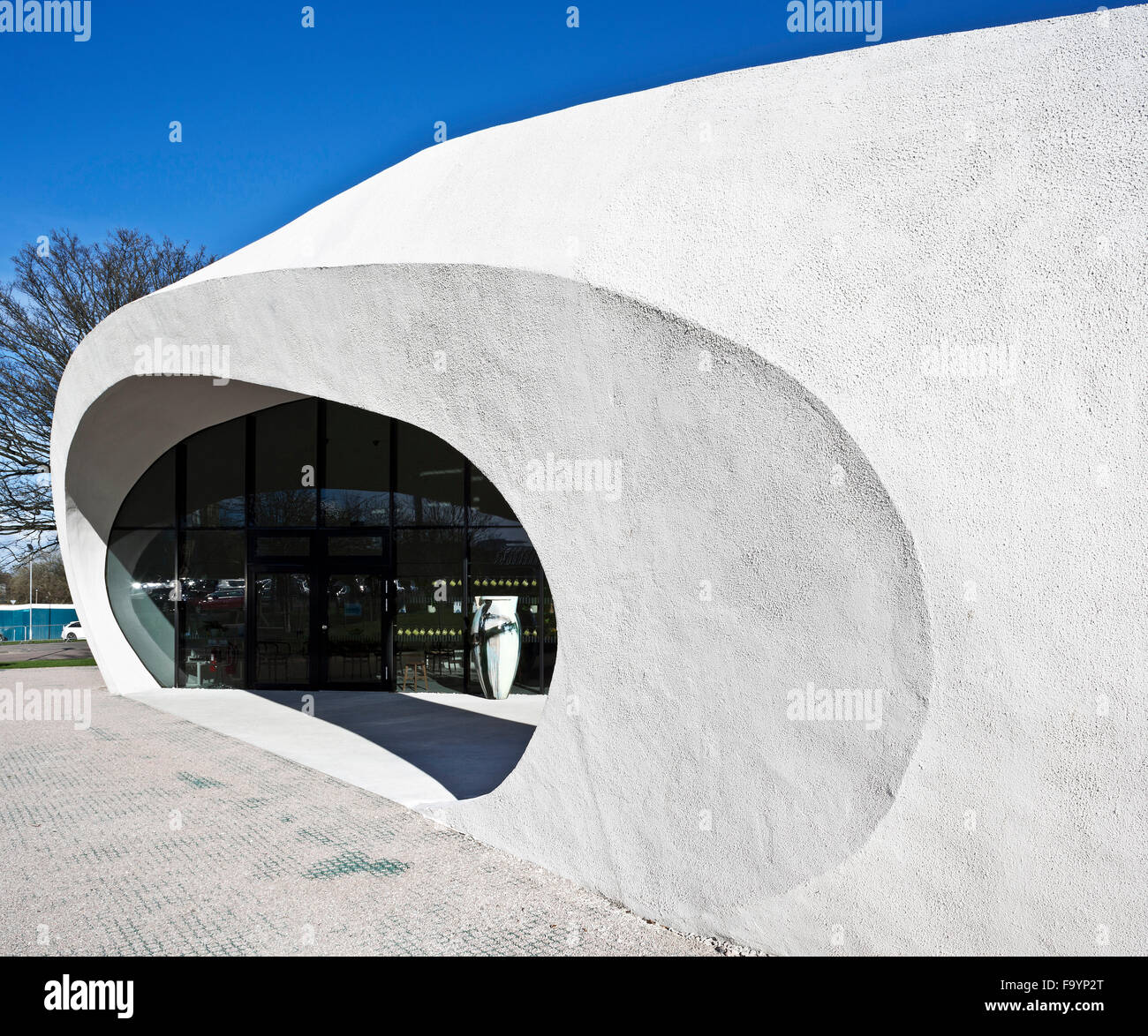 A dramatic white curved outer structure around a building which offers treatment and social spaces for cancer patients, - Stock Image
