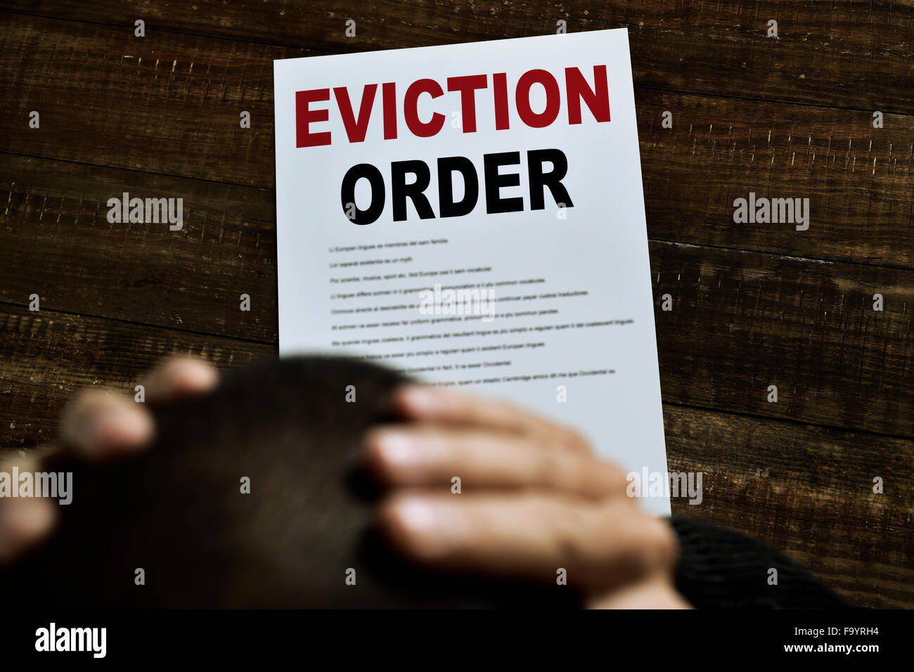 a young caucasian man with his hands in his head concerned because has just received an eviction order - Stock Image