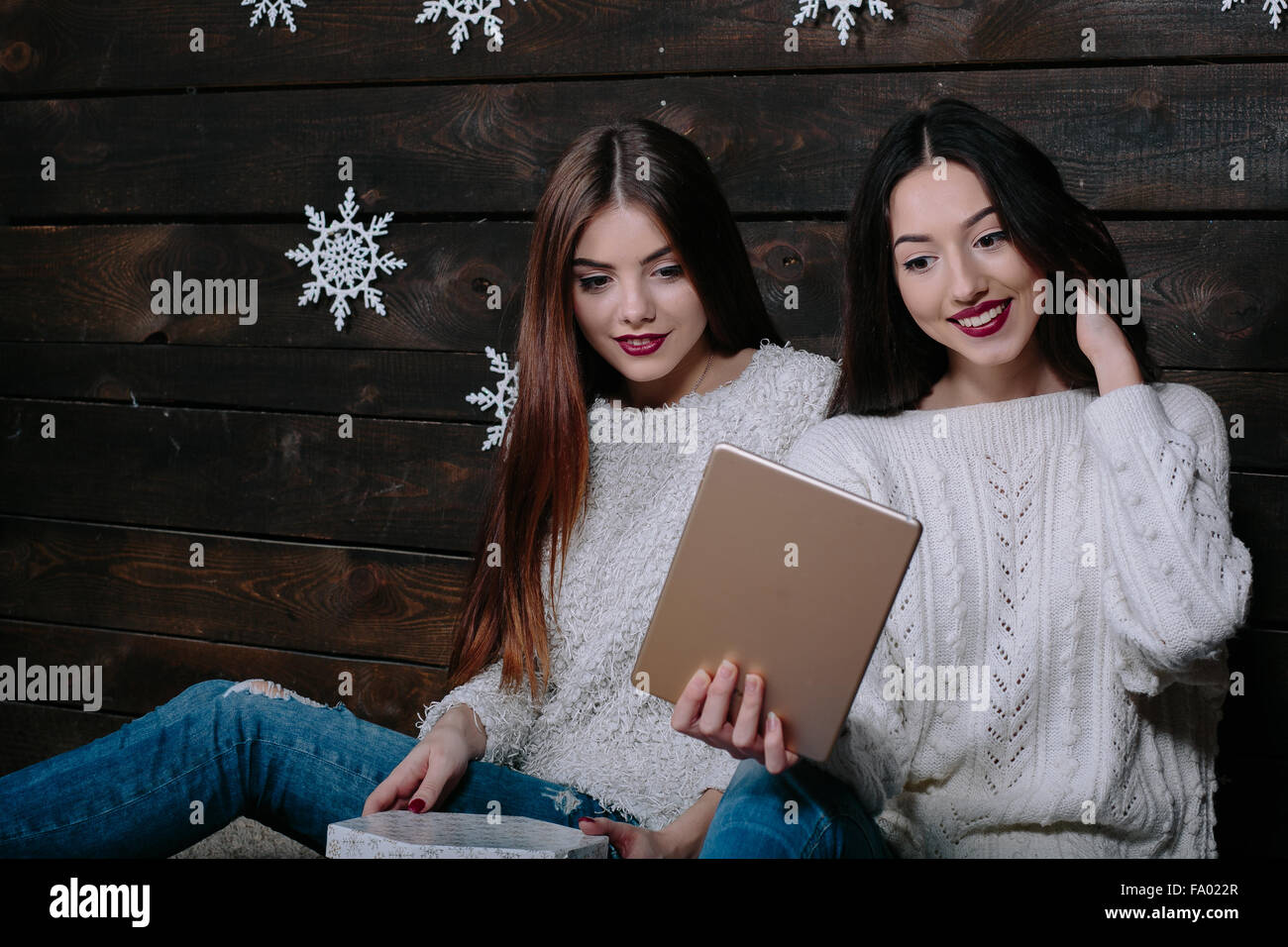 Two beautiful girls with a tablet, between gifts - Stock Image